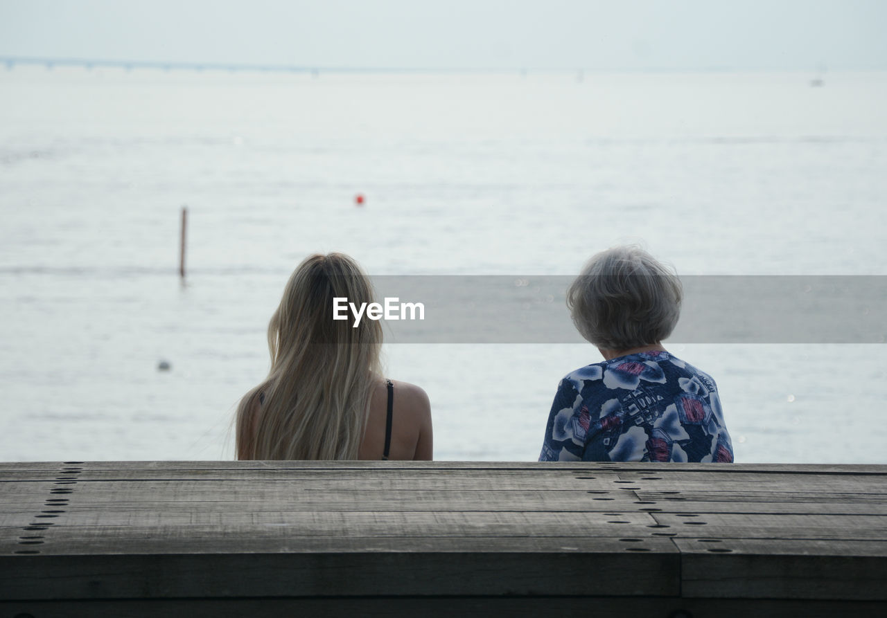 Rear View Of Grandmother Sitting With Granddaughter By Sea