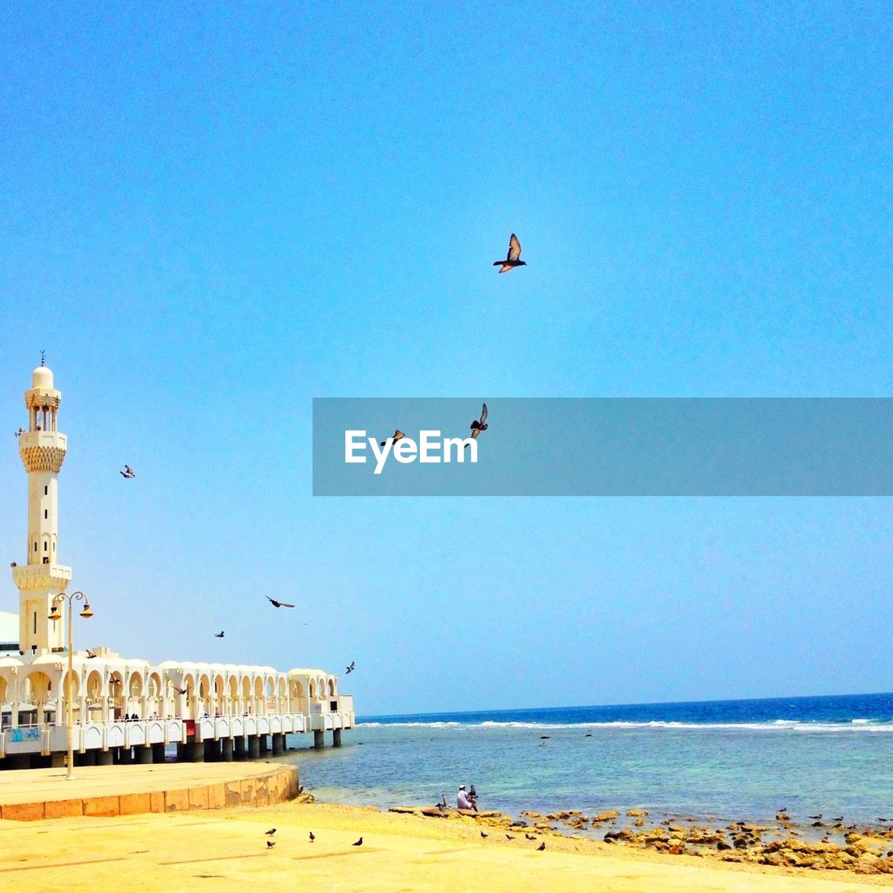 Mosque and red sea against clear sky