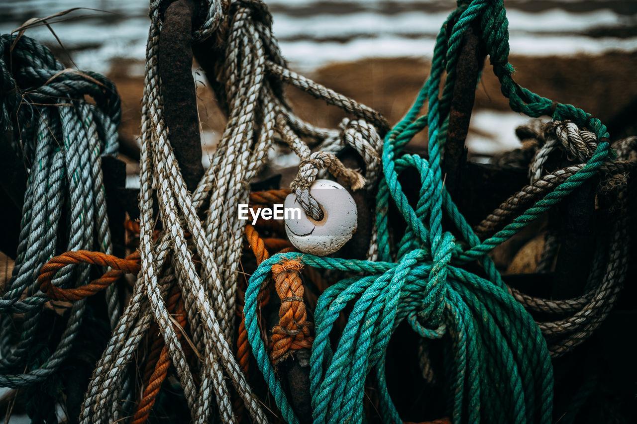 Close-up of buoys hanging at harbor