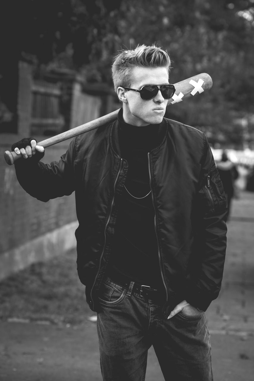Young man wearing sunglasses while standing with baseball bat on footpath