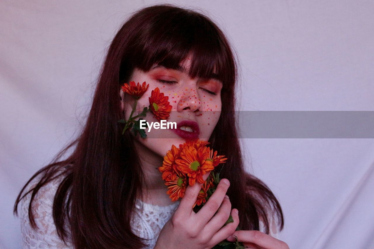Close-up of beautiful young woman with flowers on cheek