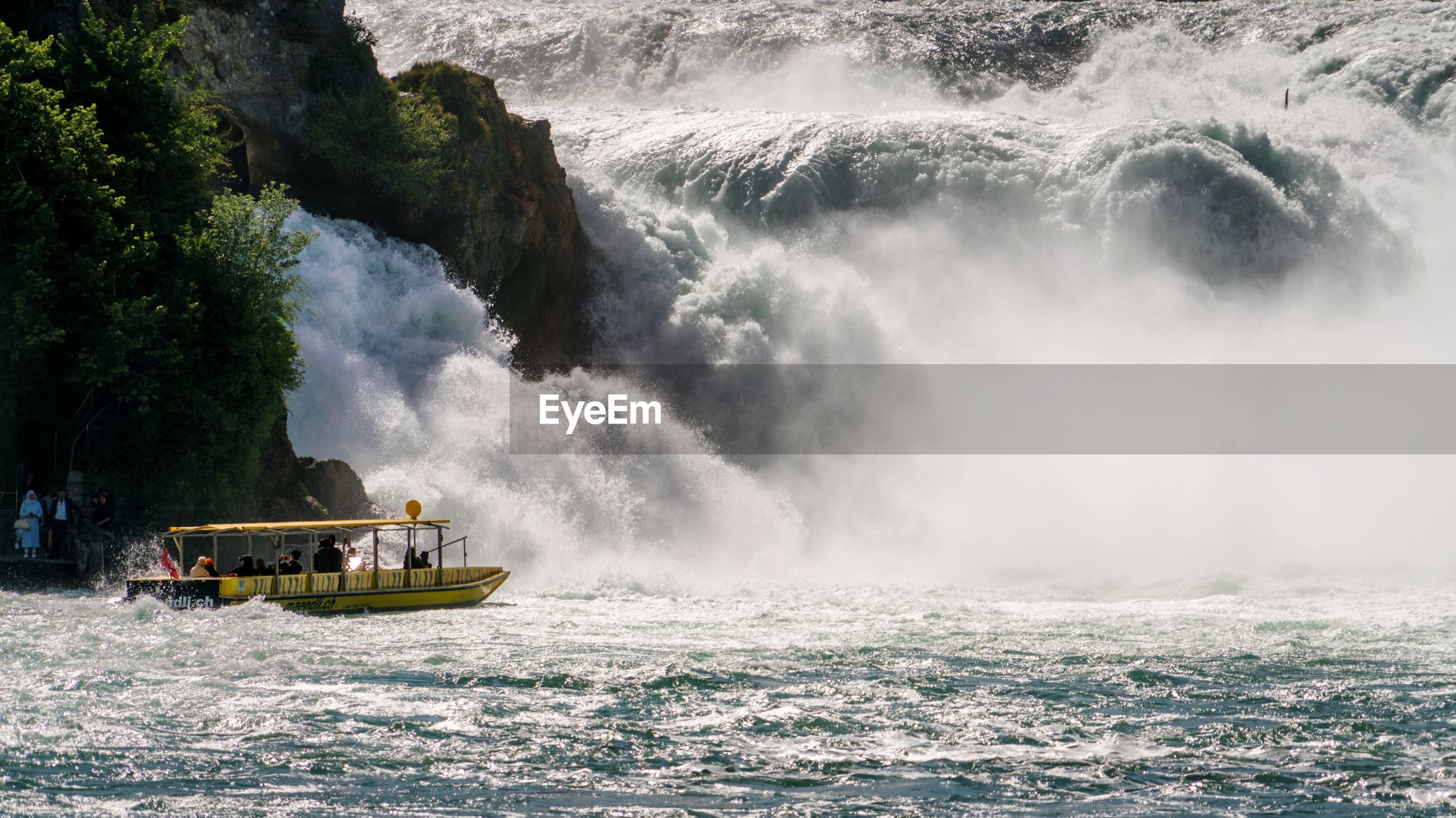 Ferry boat by waterfall in river