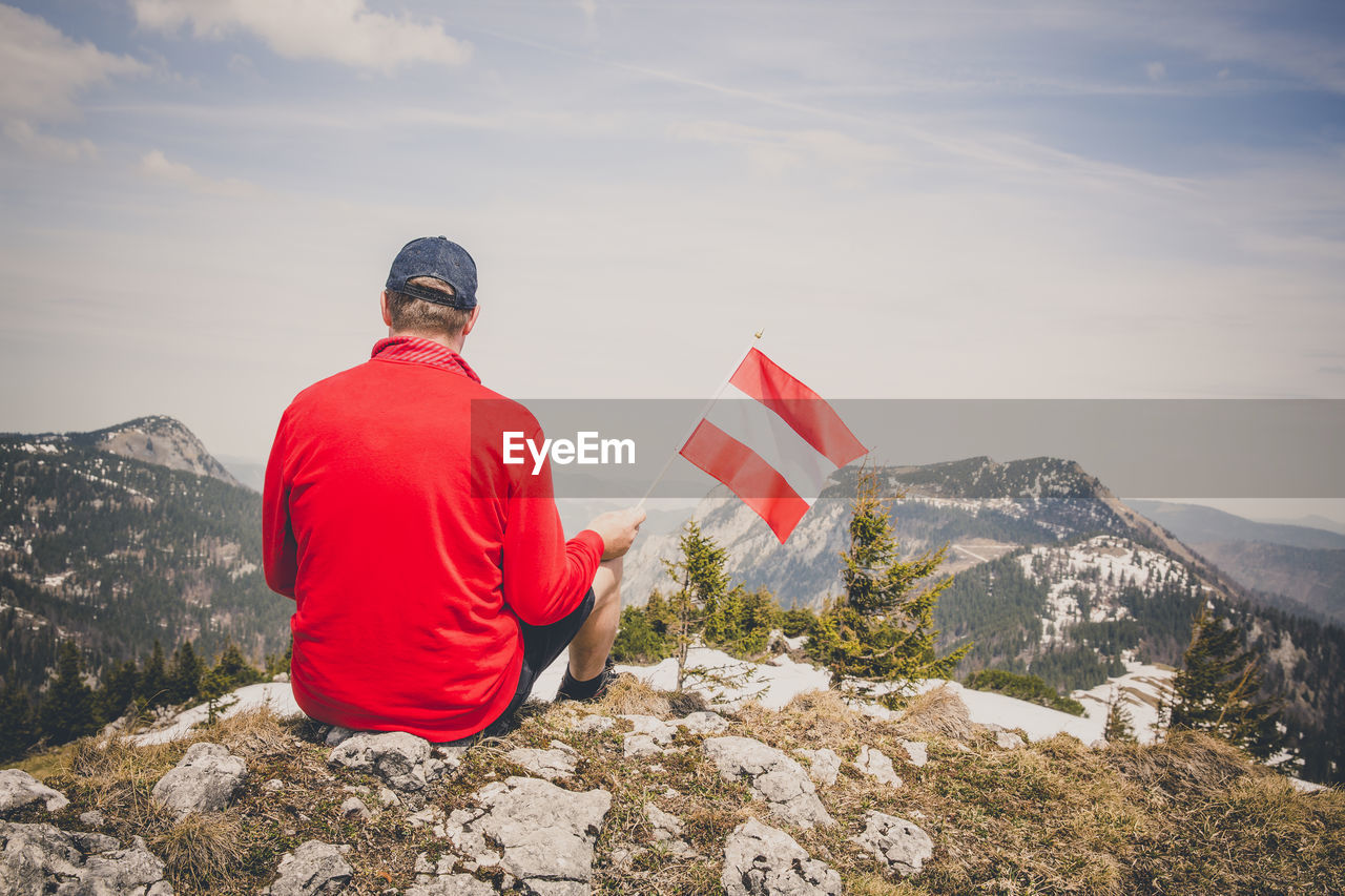 Rear View Of Man Holding Flag While Sitting On Mountain Against Sky