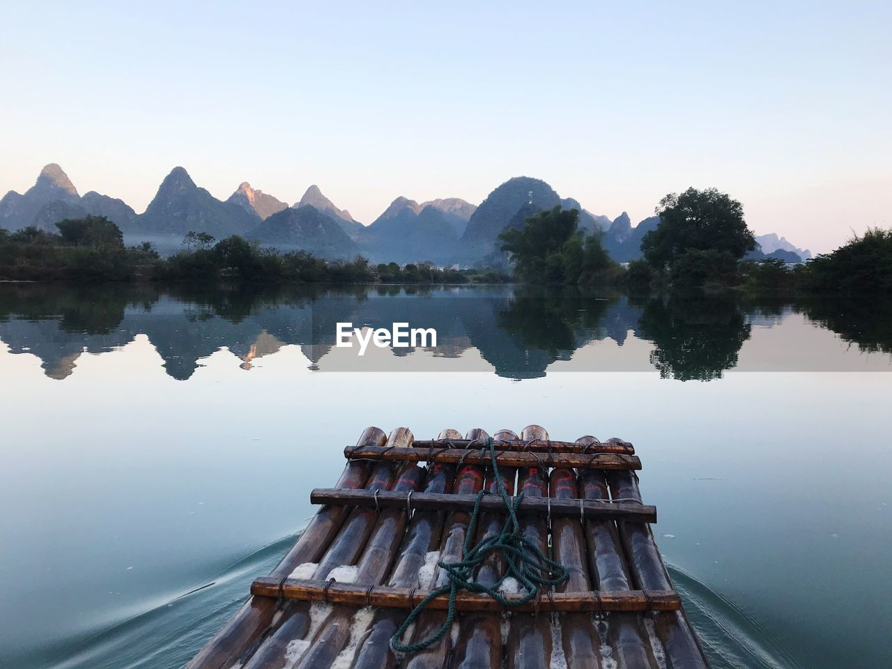 water, reflection, sky, scenics - nature, beauty in nature, lake, tranquility, nature, tranquil scene, non-urban scene, nautical vessel, idyllic, mountain, tree, clear sky, no people, transportation, mode of transportation, day, outdoors, rowboat