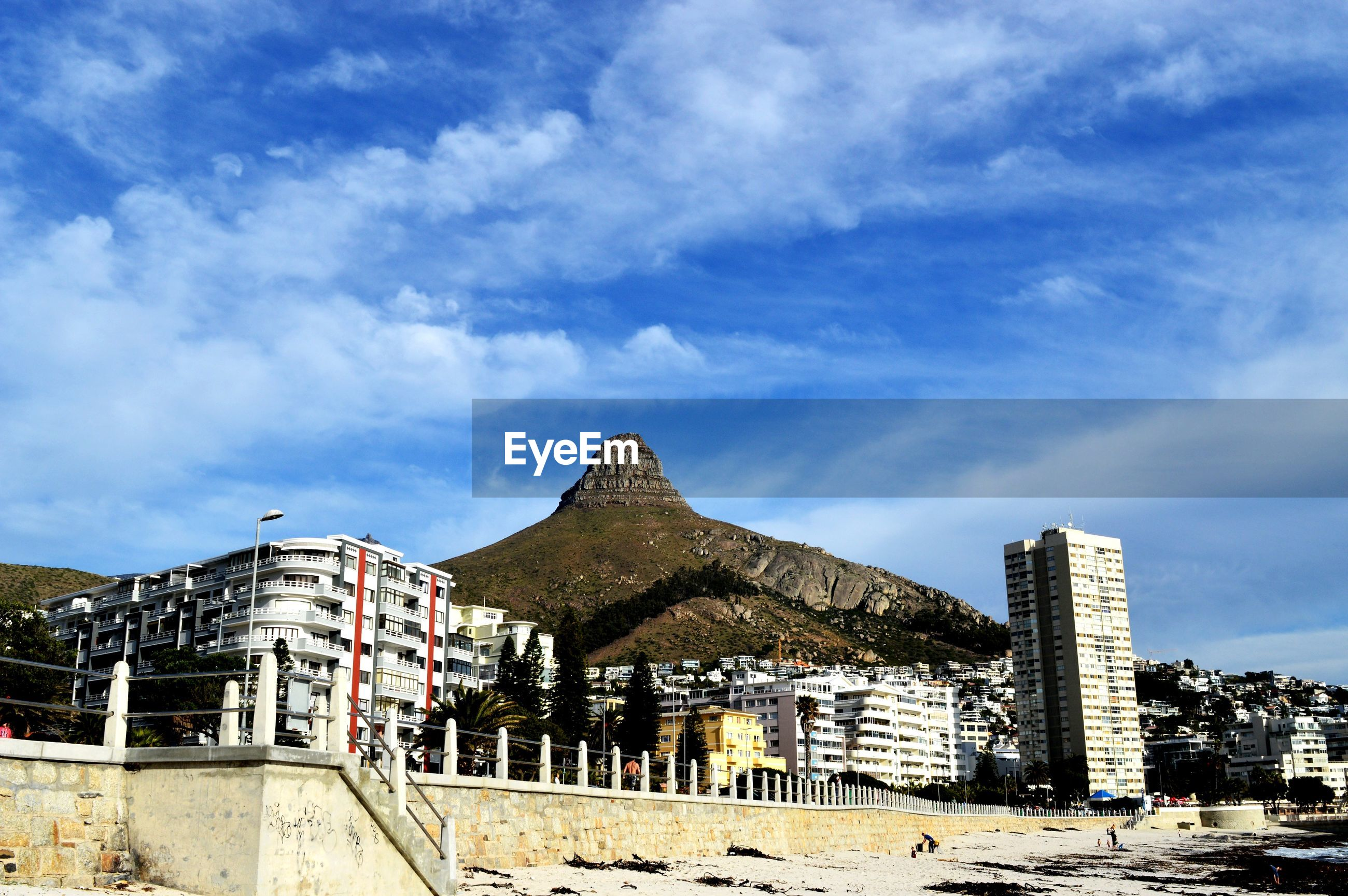 Low angle view of buildings and mountains against cloudy blue sky on sunny day