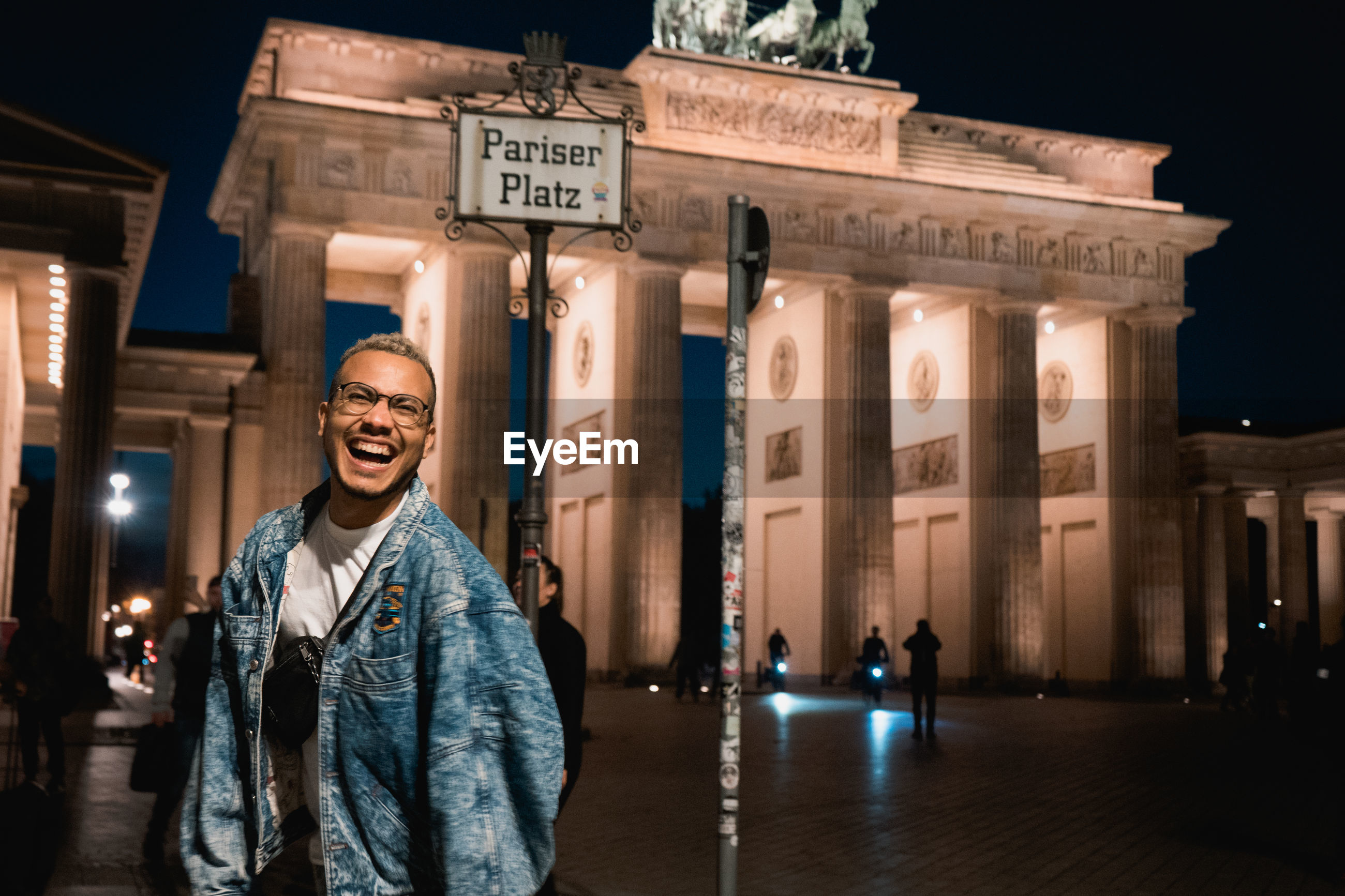 Portrait of smiling man standing in city at night