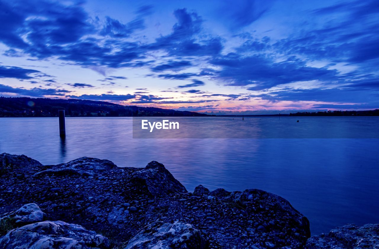 sky, water, cloud - sky, beauty in nature, scenics - nature, sunset, tranquil scene, tranquility, rock, solid, rock - object, nature, sea, blue, no people, idyllic, beach, non-urban scene, outdoors, rocky coastline