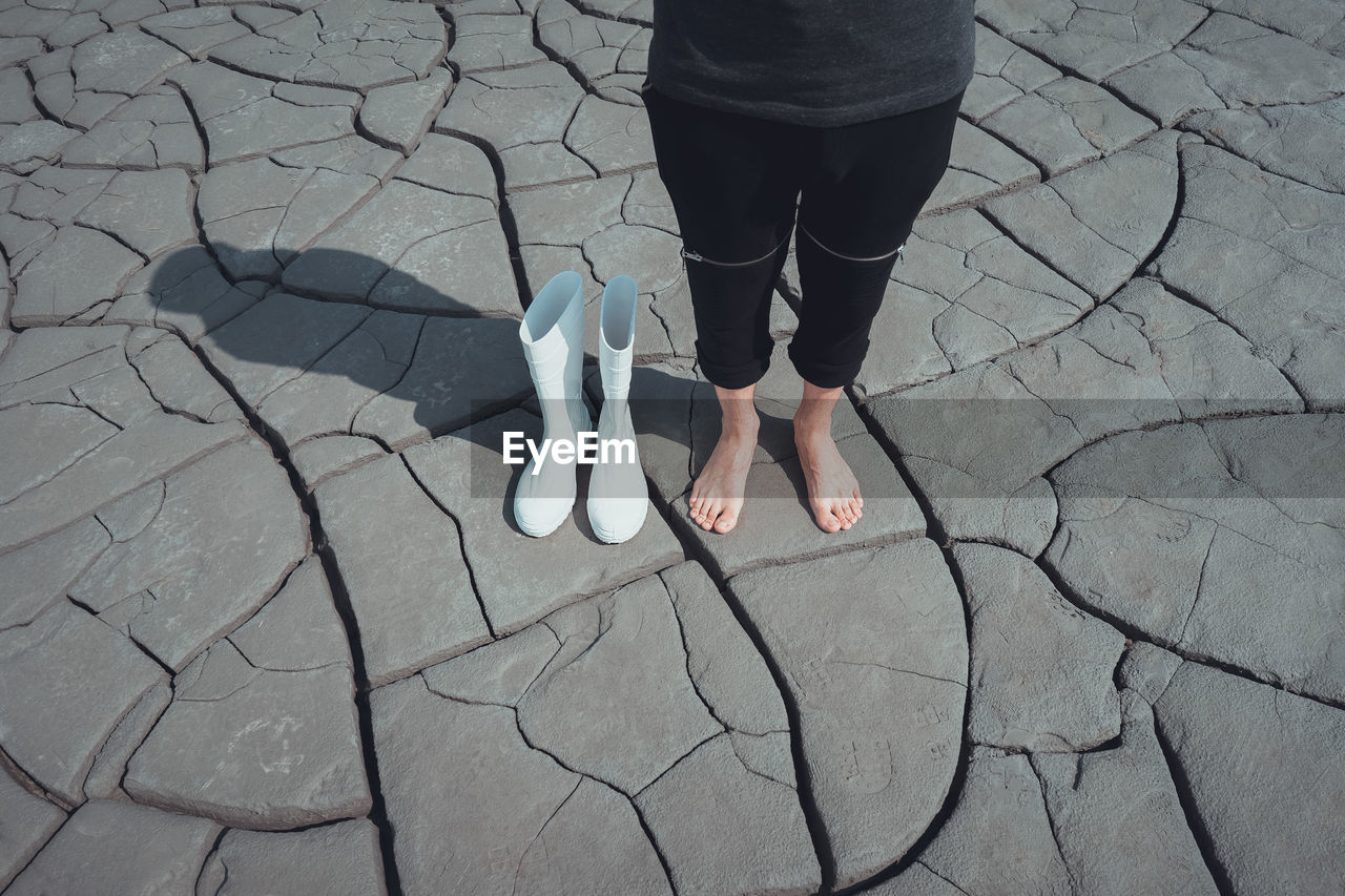 Low Section Of Woman Standing On Cracked Ground