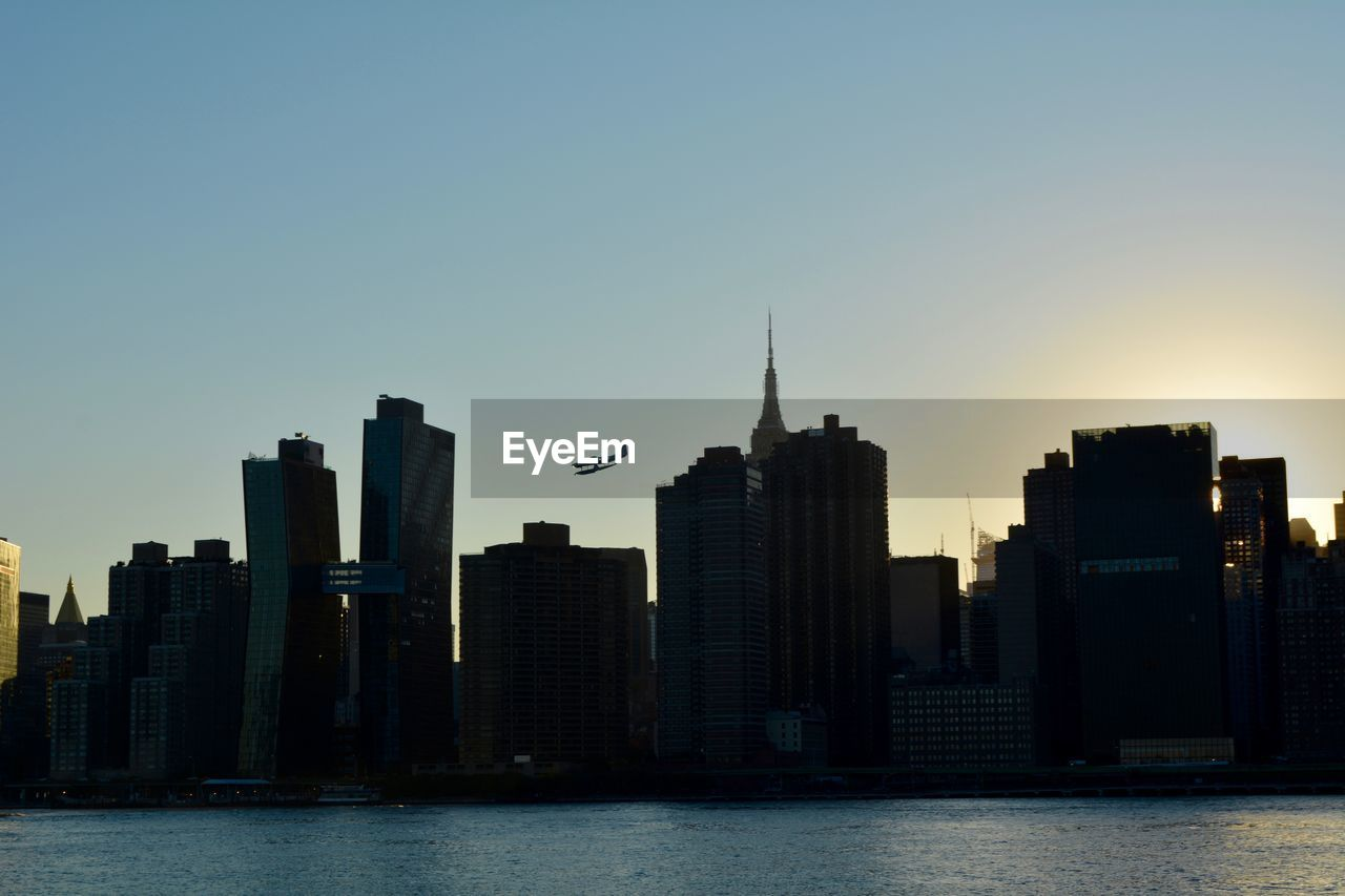 sky, building exterior, architecture, built structure, city, building, water, office building exterior, skyscraper, waterfront, clear sky, tall - high, no people, cityscape, urban skyline, landscape, nature, tower, sunset, modern, outdoors, financial district, spire