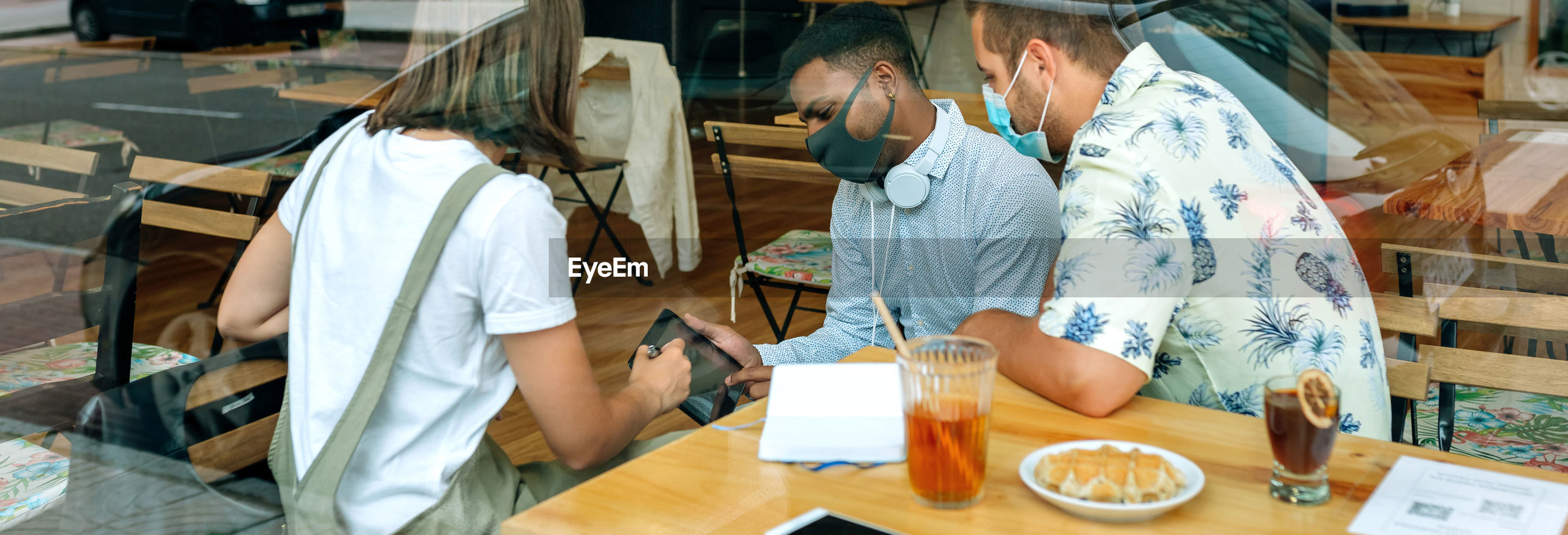 Cheerful friends wearing mask sitting at restaurant
