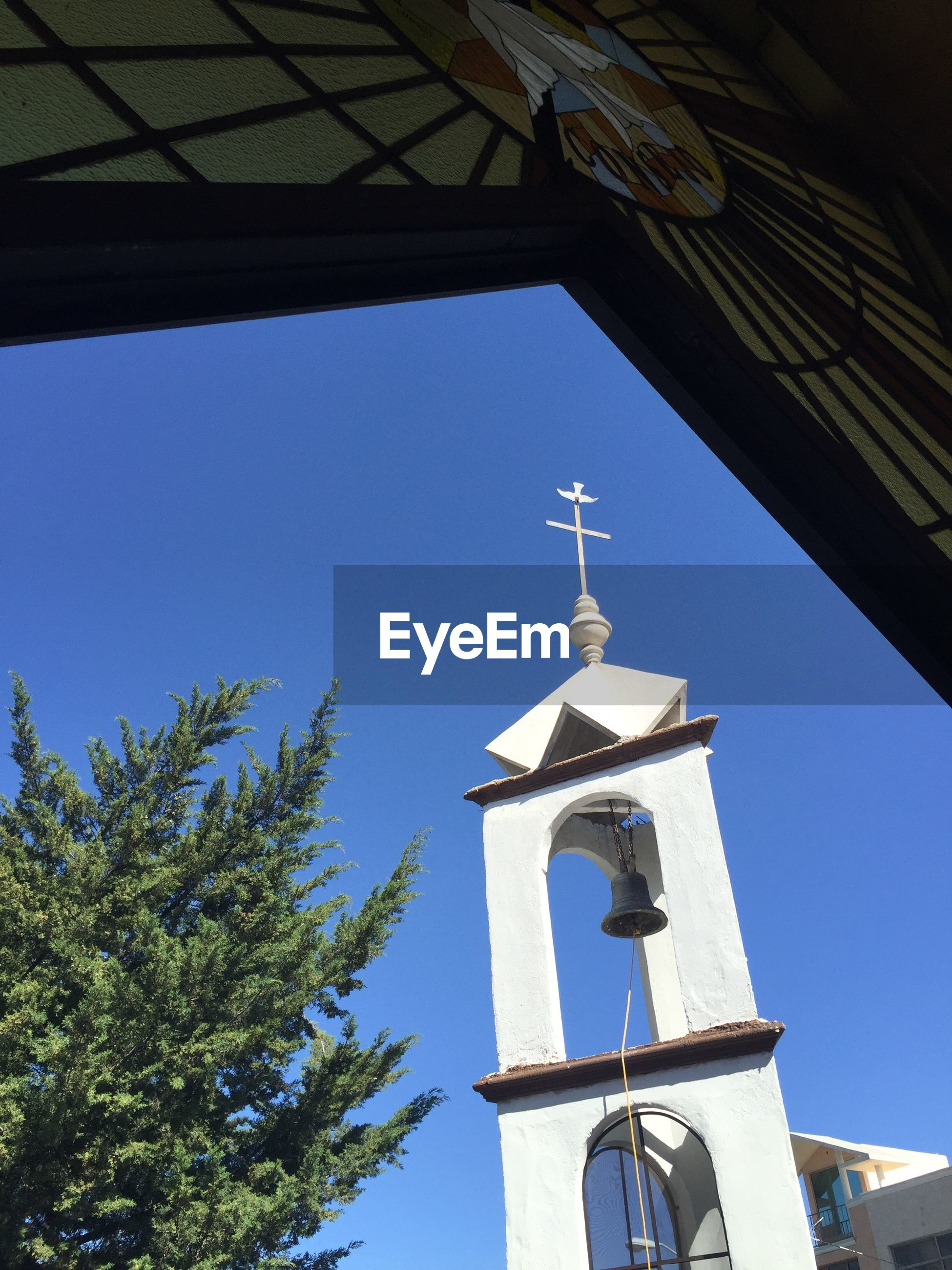 low angle view, blue, built structure, building exterior, architecture, clear sky, tree, religion, sky, cross, sunlight, church, day, outdoors, no people, spirituality, place of worship, nature