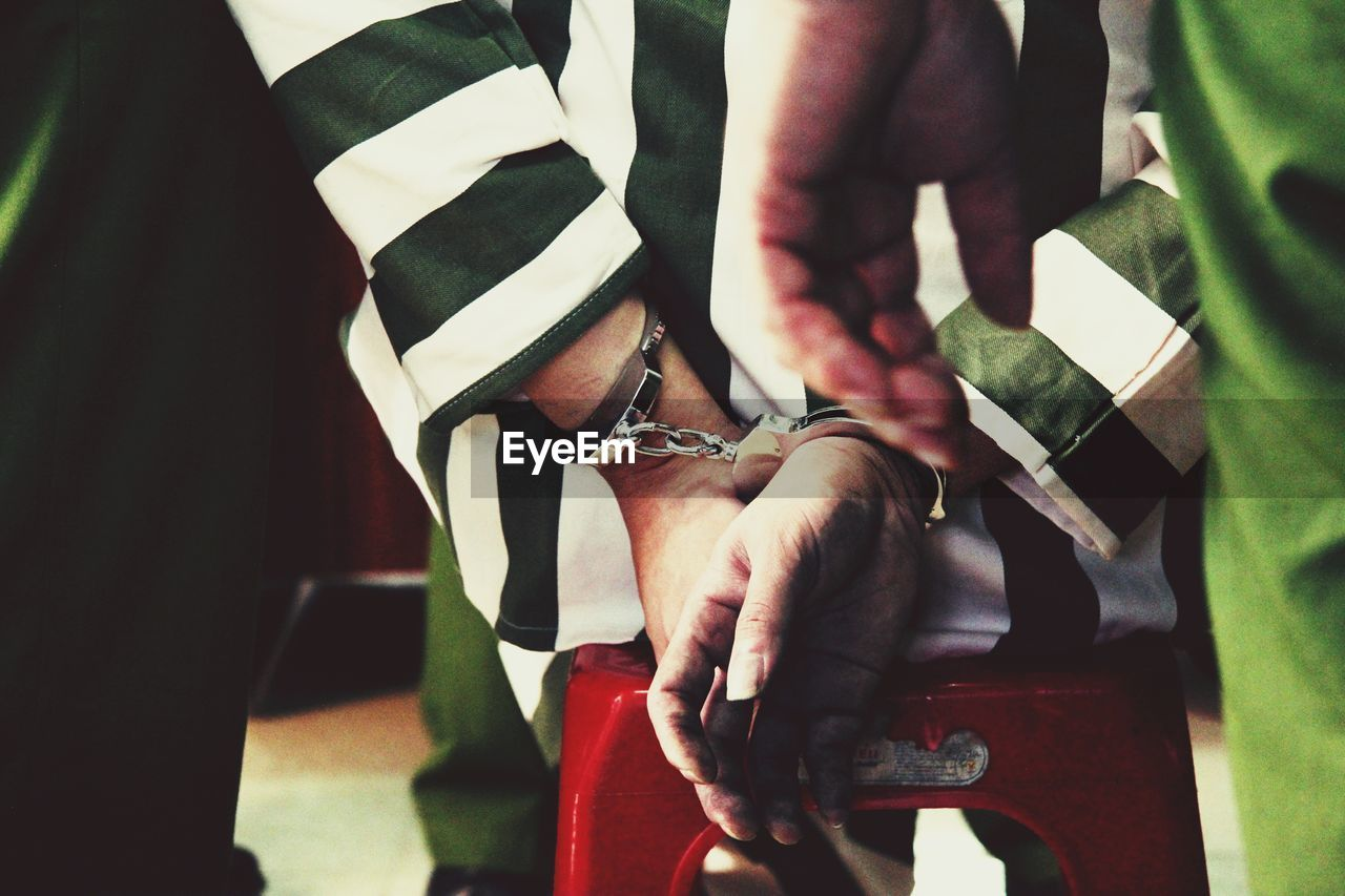 Rear View Of Criminal Hands Trapped In Handcuffs