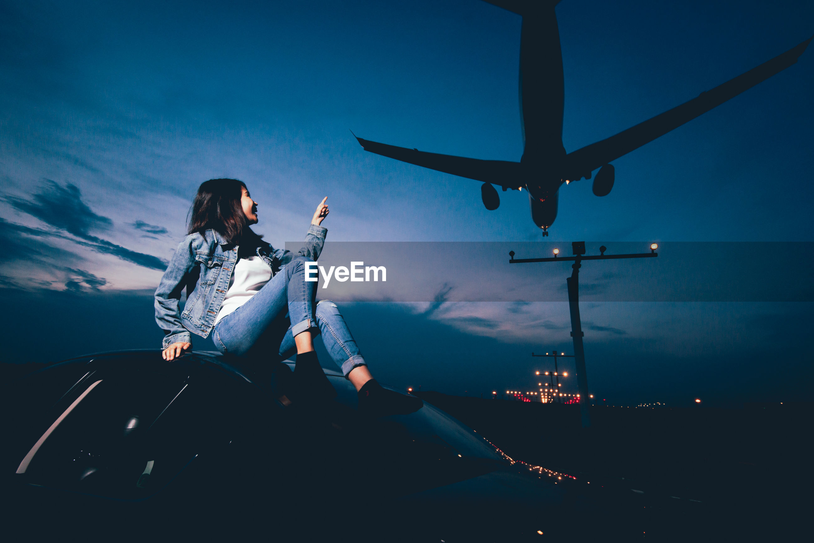 Smiling woman sitting on car with airplane landing at airport against blue sky