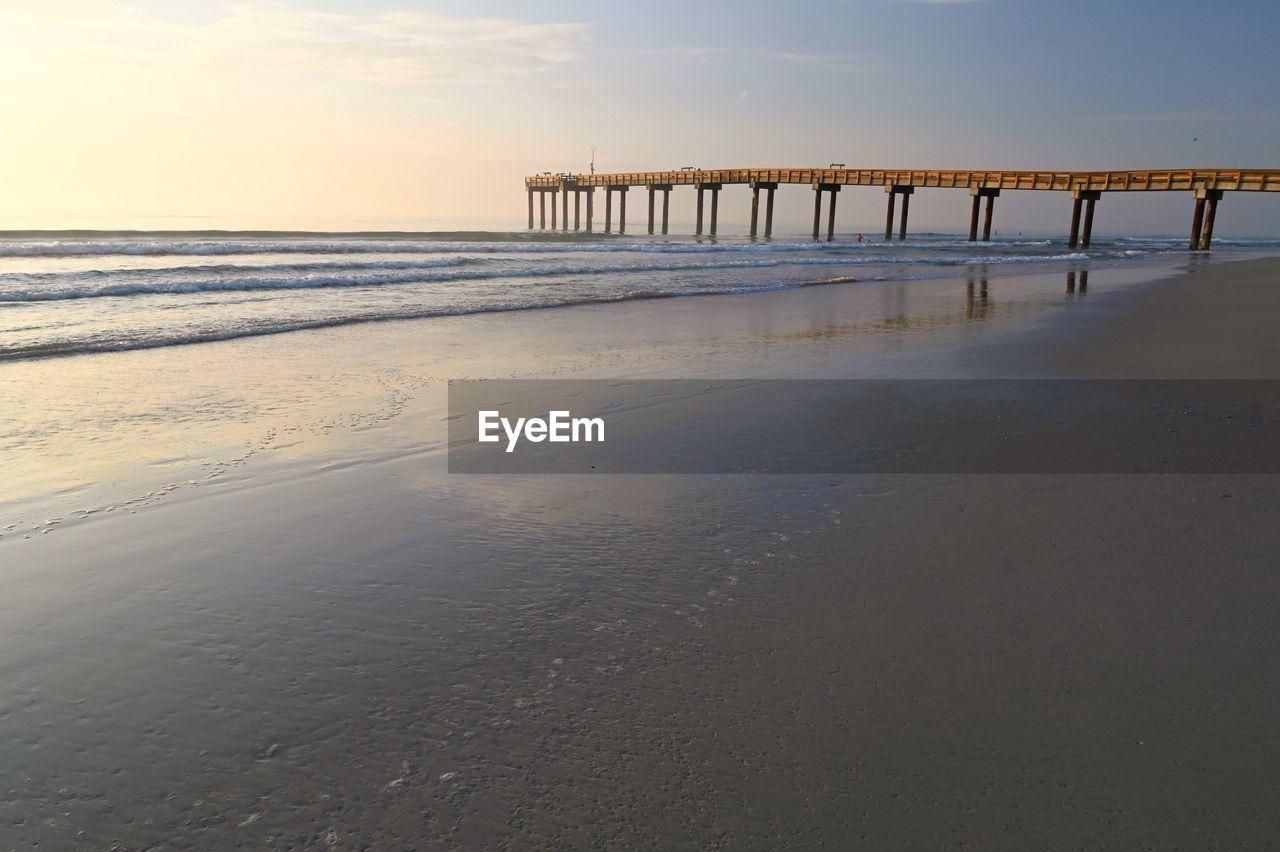 PIER ON BEACH AGAINST SKY AT SUNSET
