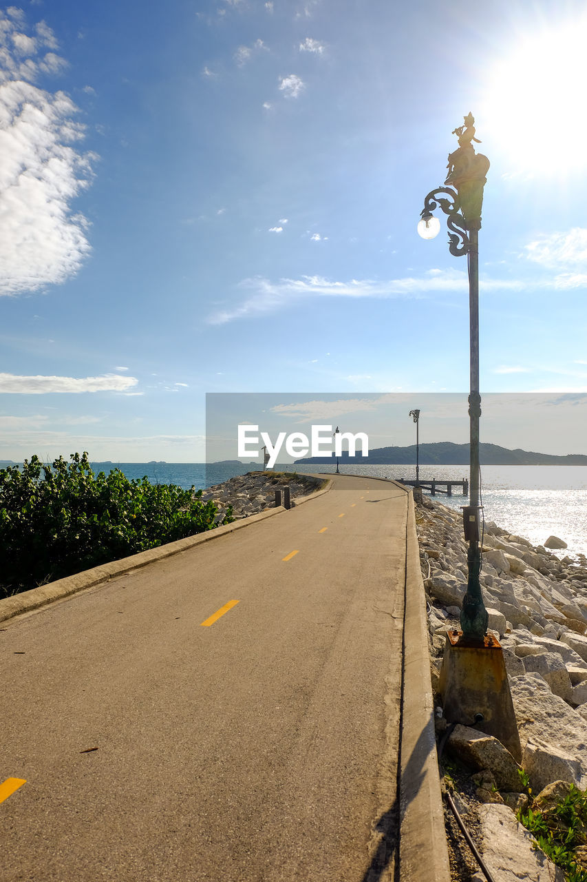 sky, water, street, sea, road, cloud - sky, street light, nature, sunlight, direction, transportation, beauty in nature, the way forward, scenics - nature, land, day, lighting equipment, no people, beach, horizon over water, outdoors