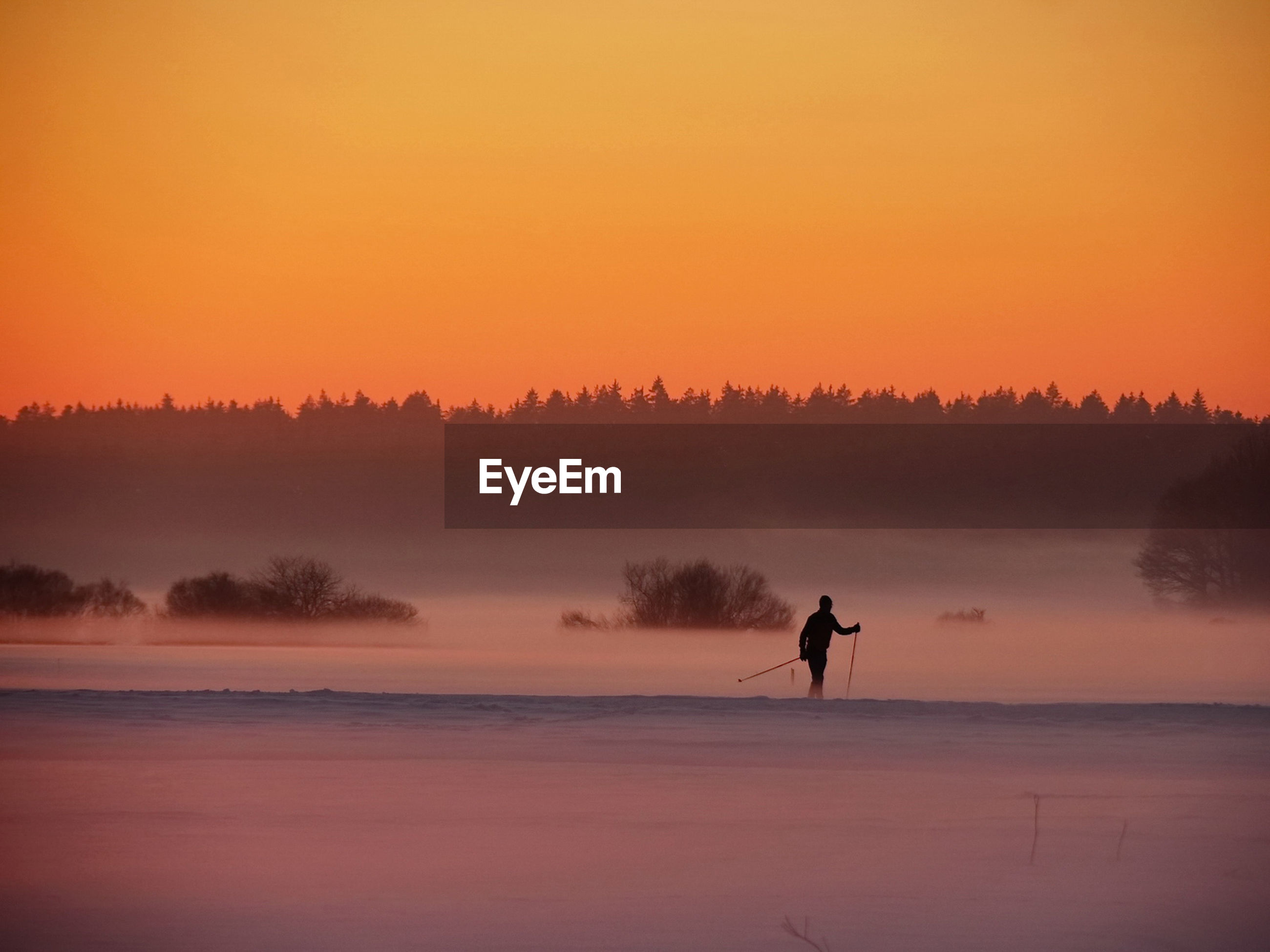 Silhouette man skiing on field against clear orange sky during sunset