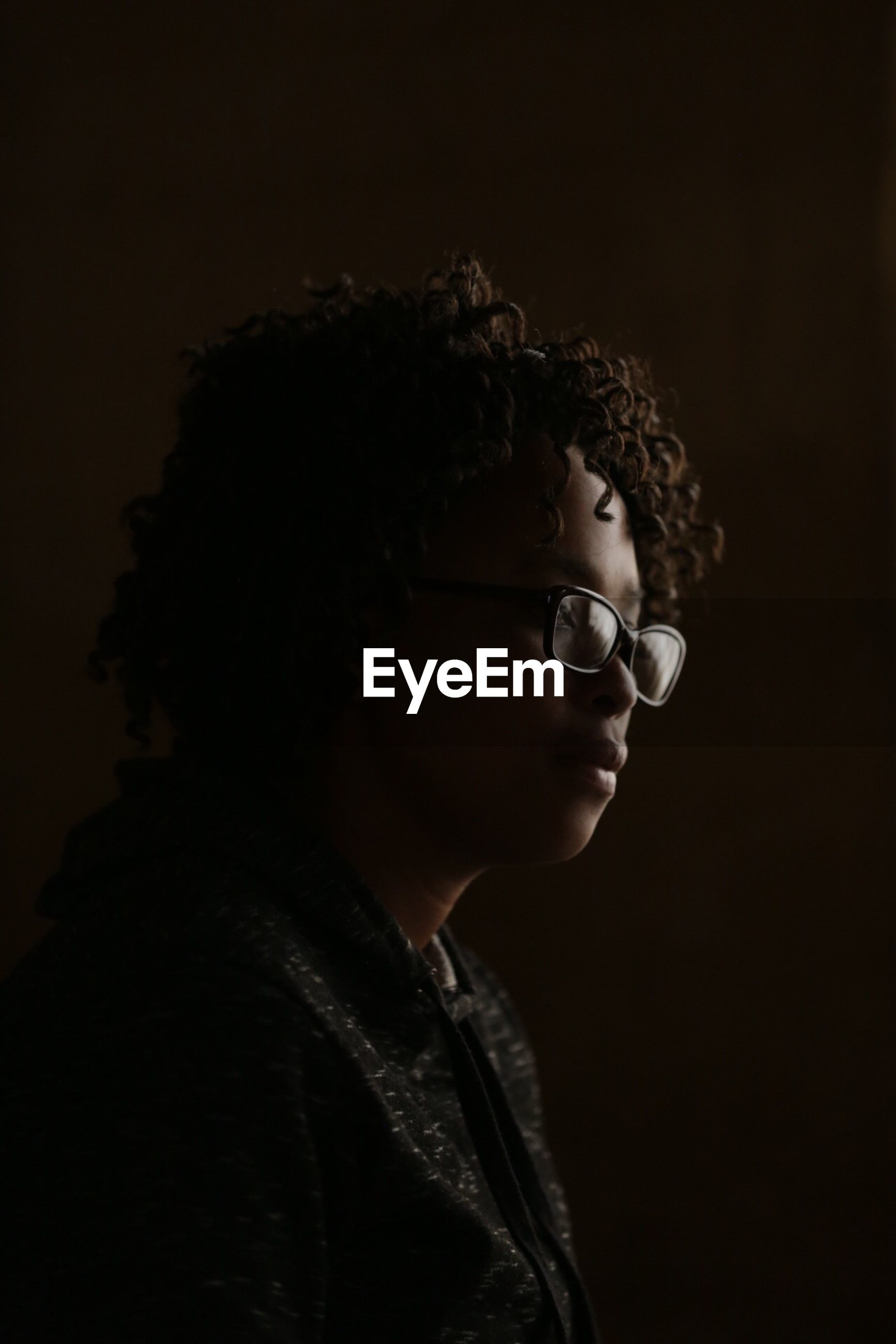 eyeglasses, studio shot, one person, curly hair, brown background, side view, young adult, real people, headshot, indoors, black background, young women, close-up, people