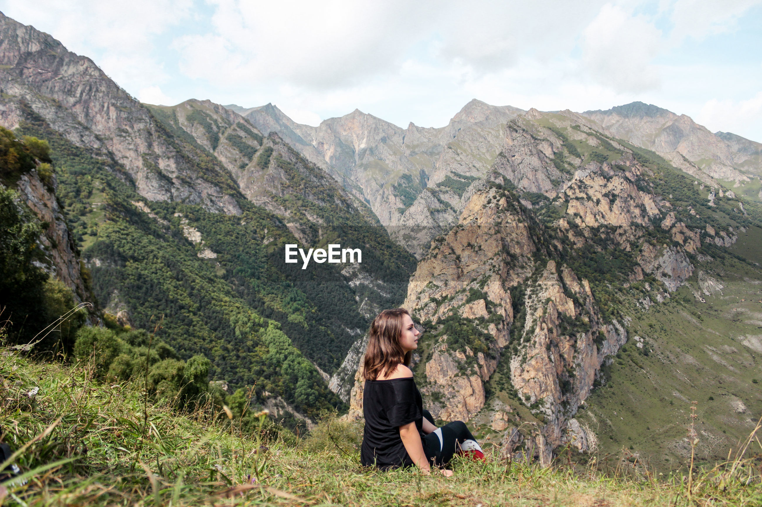 Side view of young woman sitting against mountain range