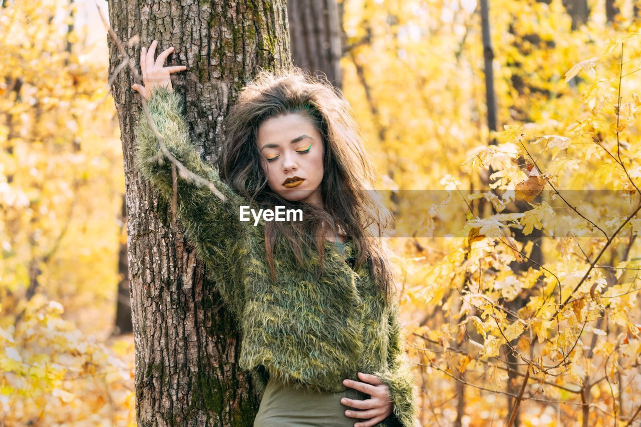 Young Woman Standing Against Tree Trunk In Forest During Autumn