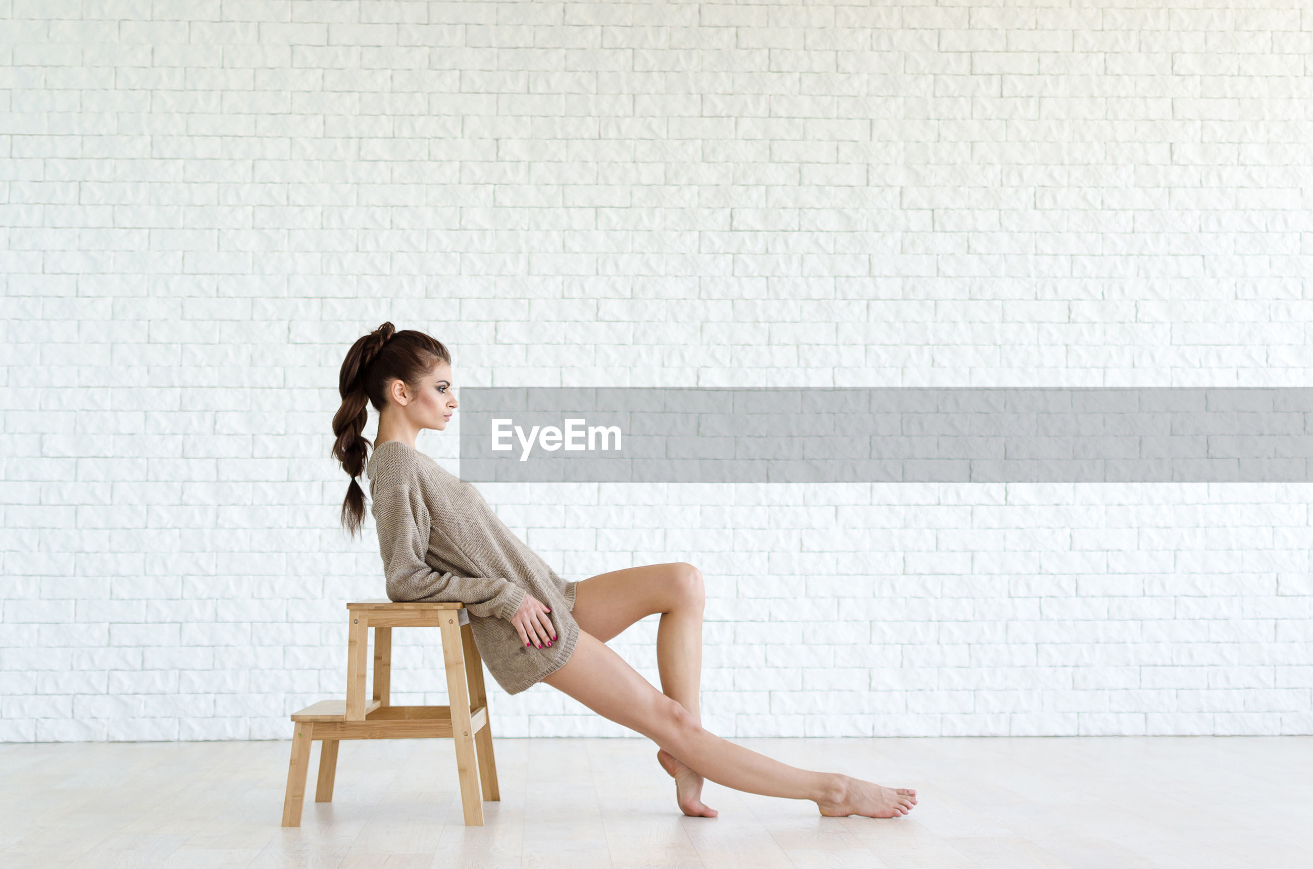 Full length of beautiful woman leaning on stool against brick wall