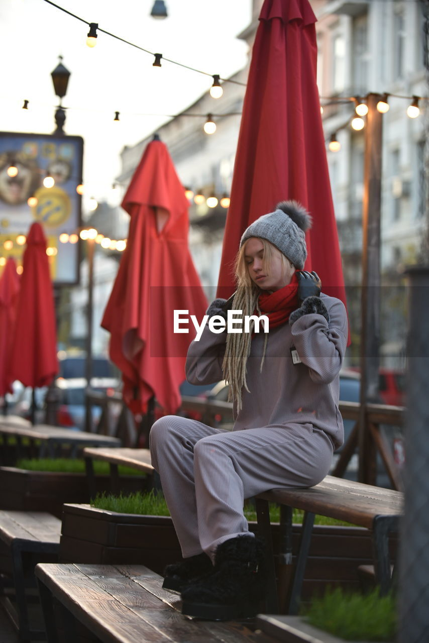Woman in warm clothes while sitting on bench in city