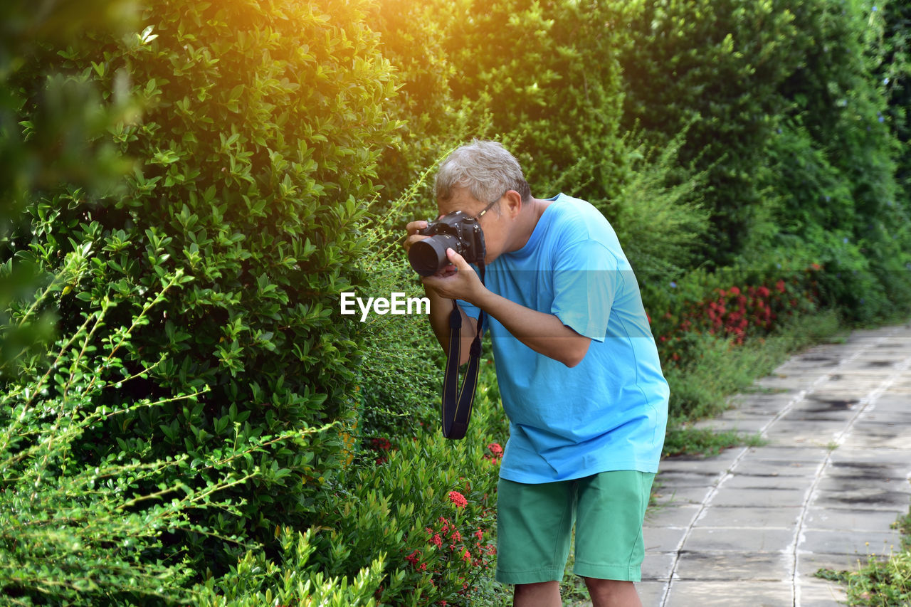 Mature Man Photographing Plants At Park