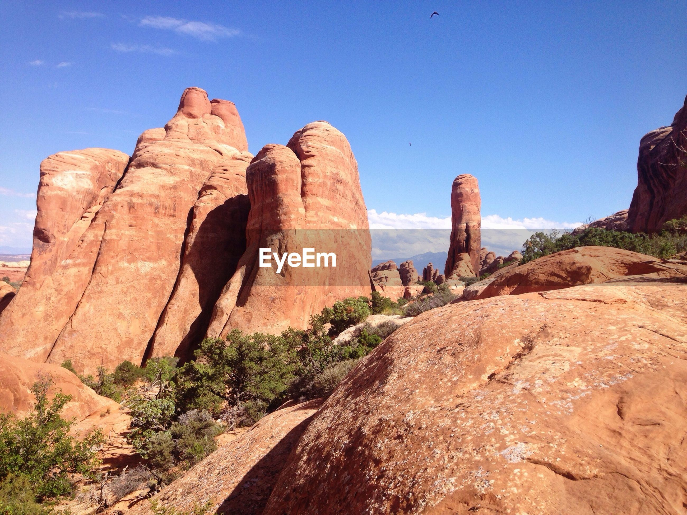 Low angle view of rock formations against blue sky on sunny day