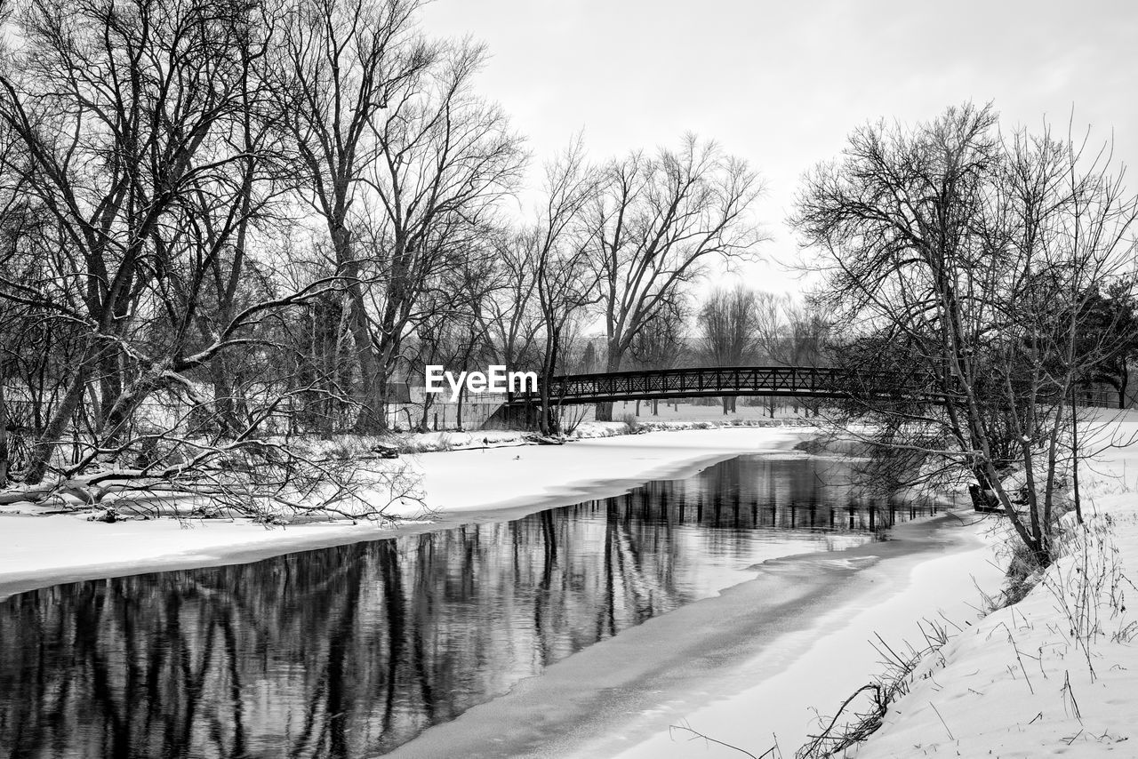Bare Trees On Snow Covered Field By Canal Against Sky