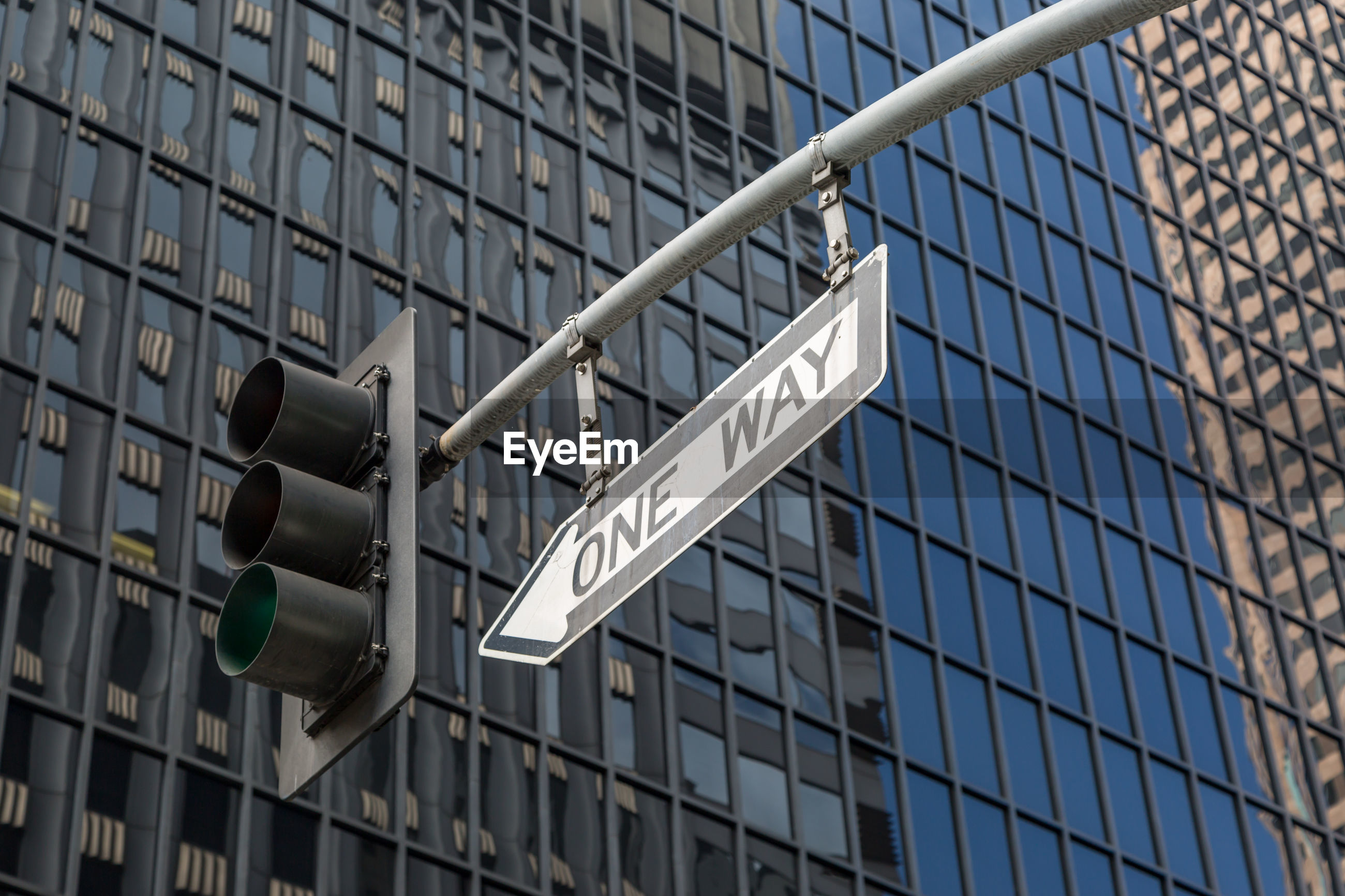Low angle view of directional sign with stoplight against modern building in city