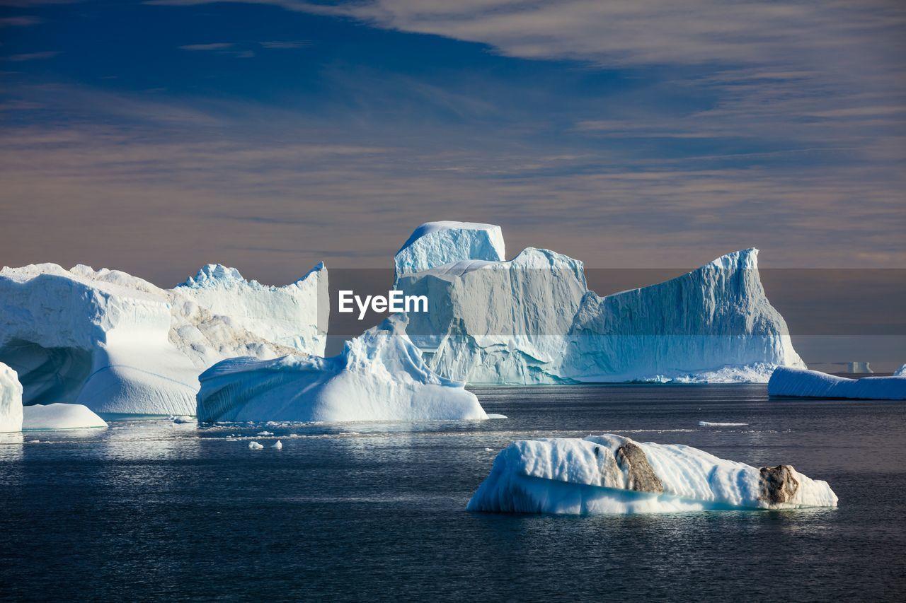 Icebergs on sea against sky