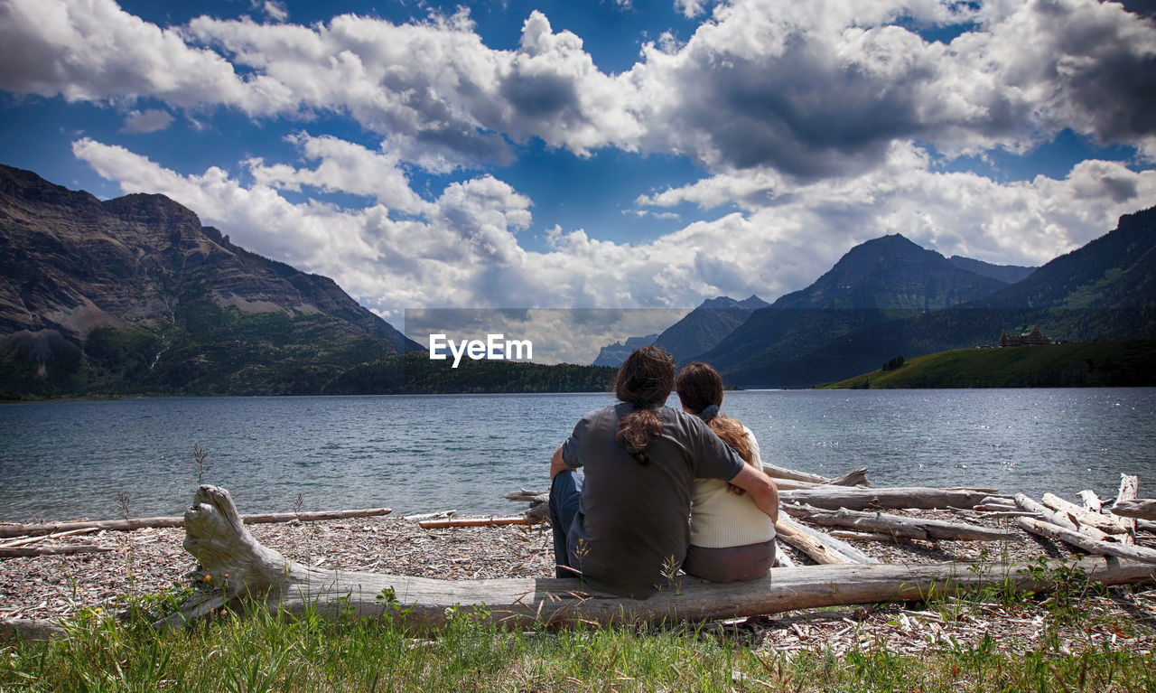 Rear View Of Couple Sitting At Lakeshore Against Cloudy Sky