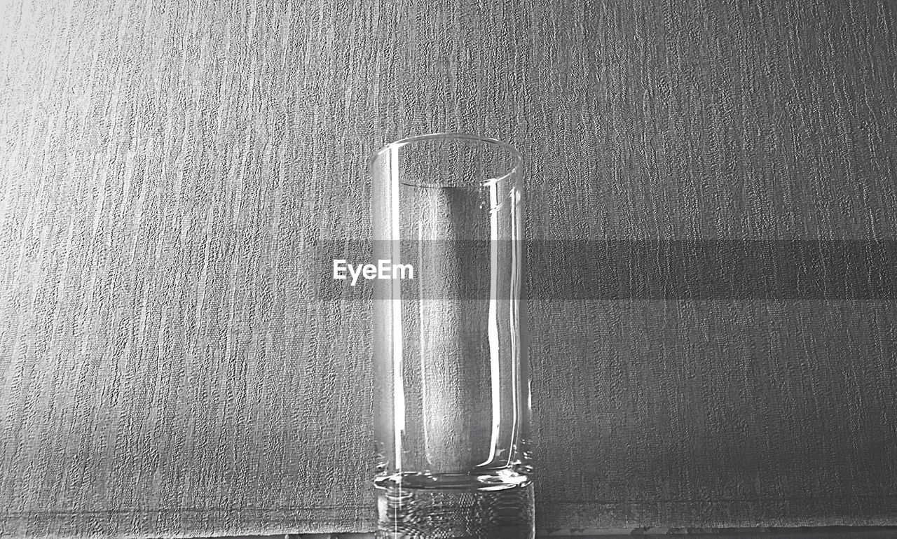 Close-Up Of Empty Glass By Wall