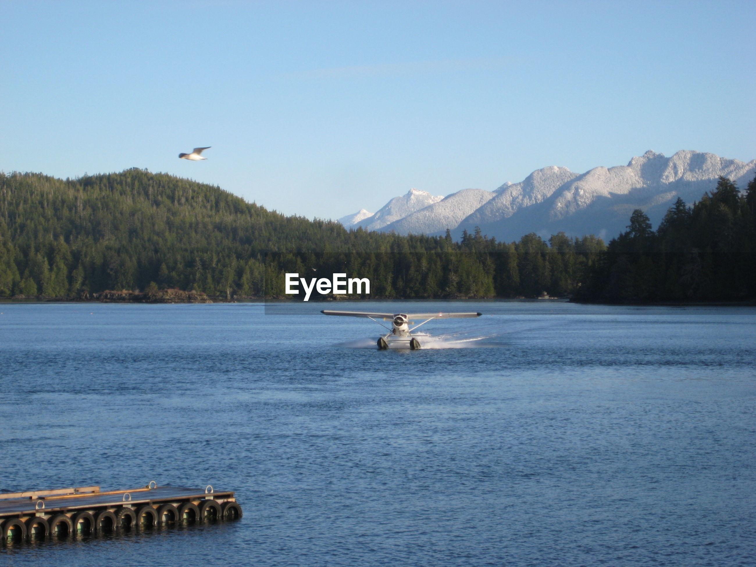 Seaplane over lake against sky