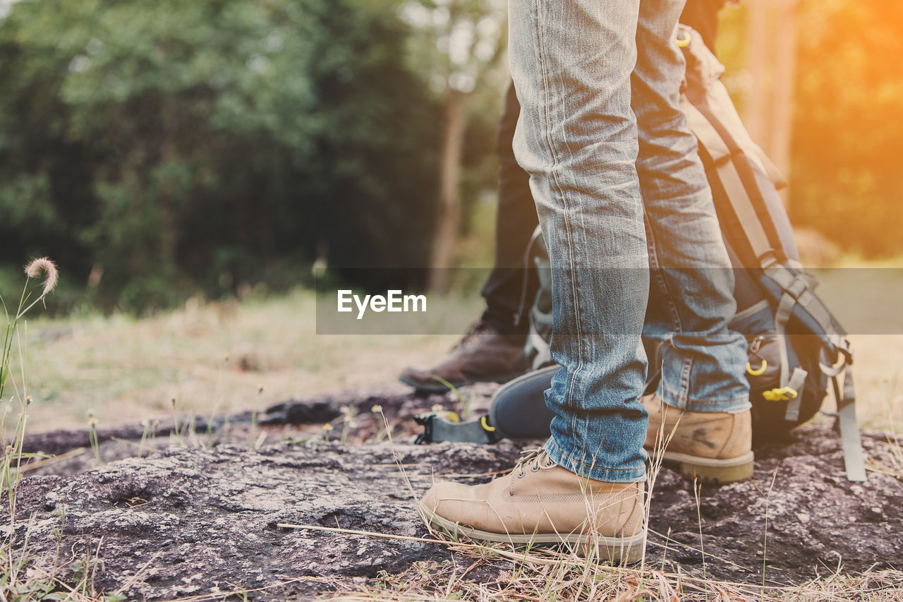 low section, one person, human leg, lifestyles, real people, human body part, nature, body part, shoe, land, day, leisure activity, focus on foreground, casual clothing, field, men, outdoors, standing, sunlight, jeans, human limb, human foot
