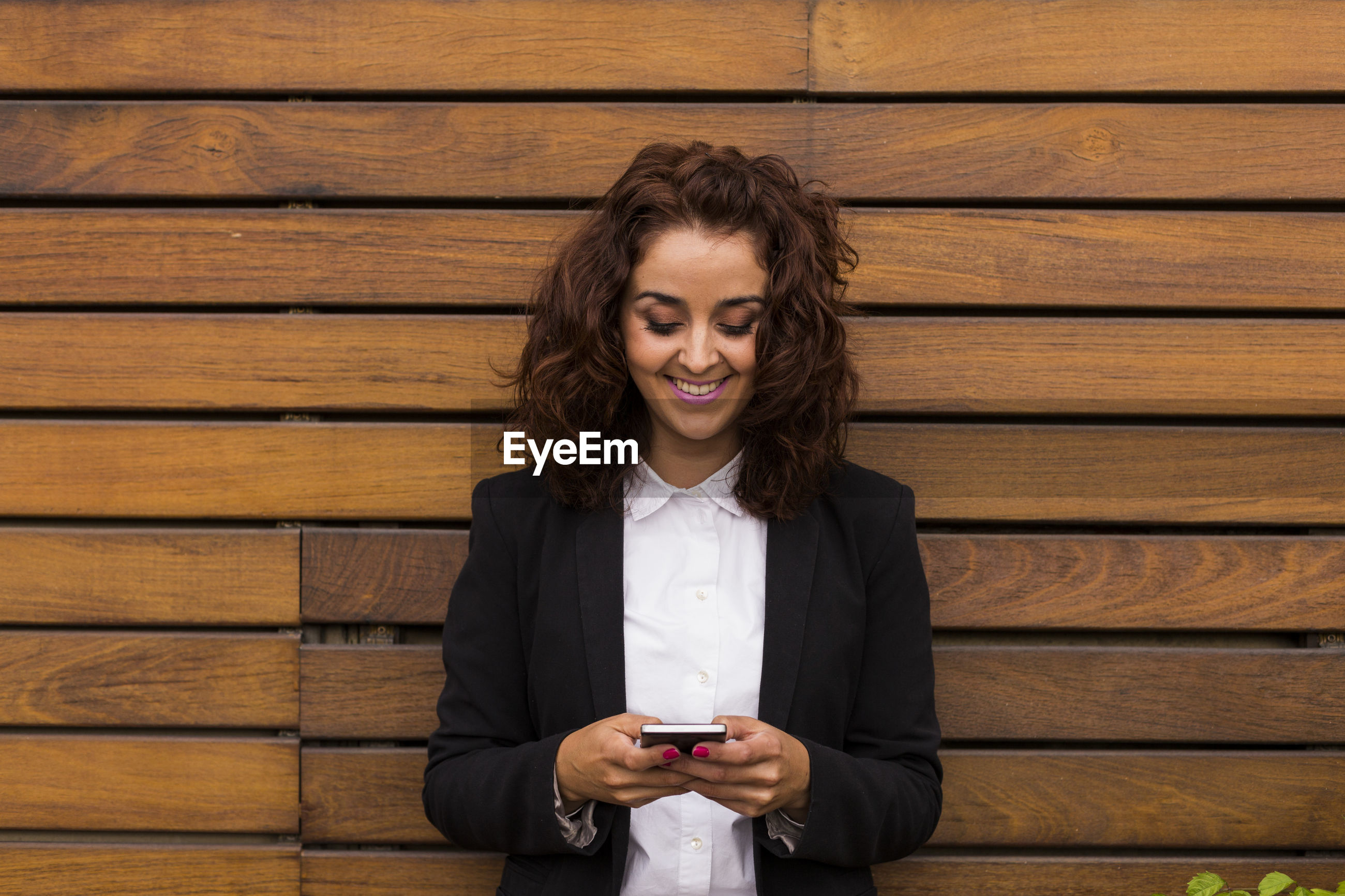 Businesswoman using mobile phone against wooden wall