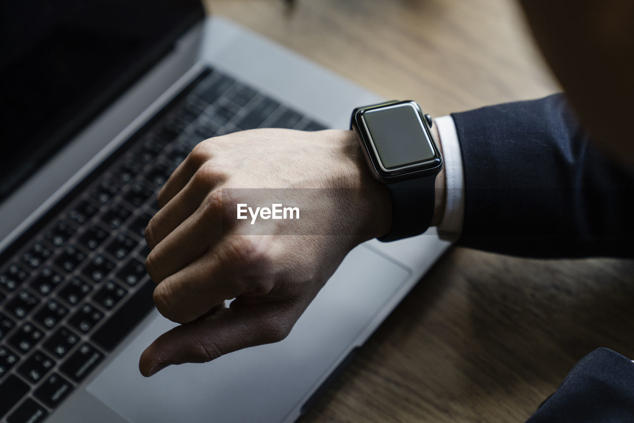 Cropped hand of man checking time against laptop