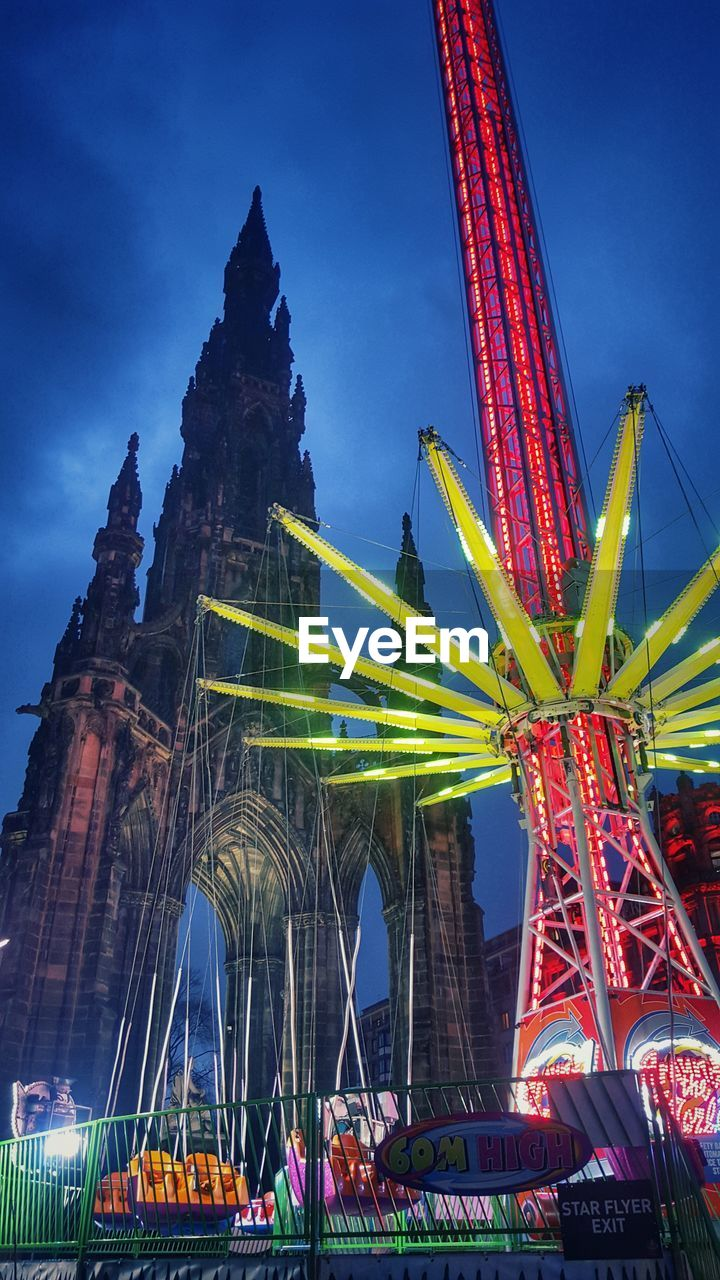 Low Angle View Of Chain Swing Ride And Scott Monument Against Sky At Dusk