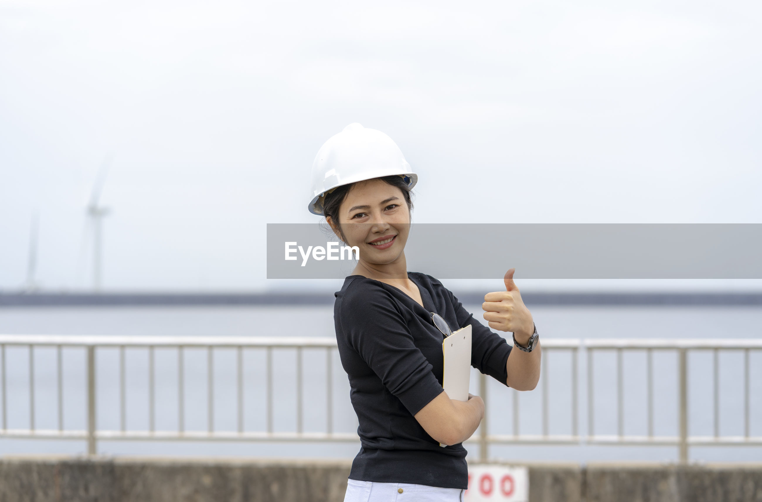 Portrait of smiling woman gesturing thumbs up while holding clipboard against railing and sky