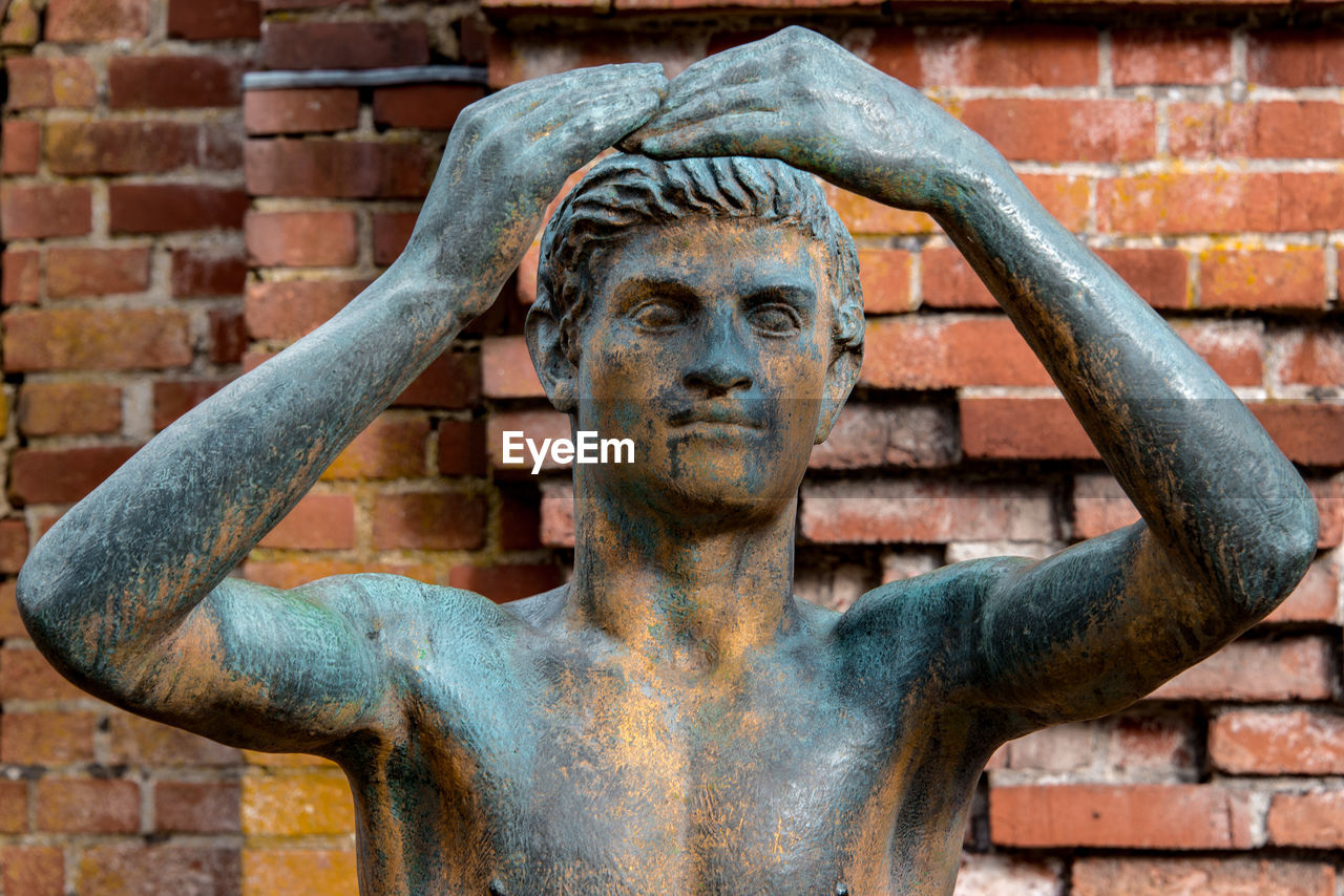 brick wall, statue, outdoors, architecture, day, building exterior, sculpture, built structure, no people, close-up