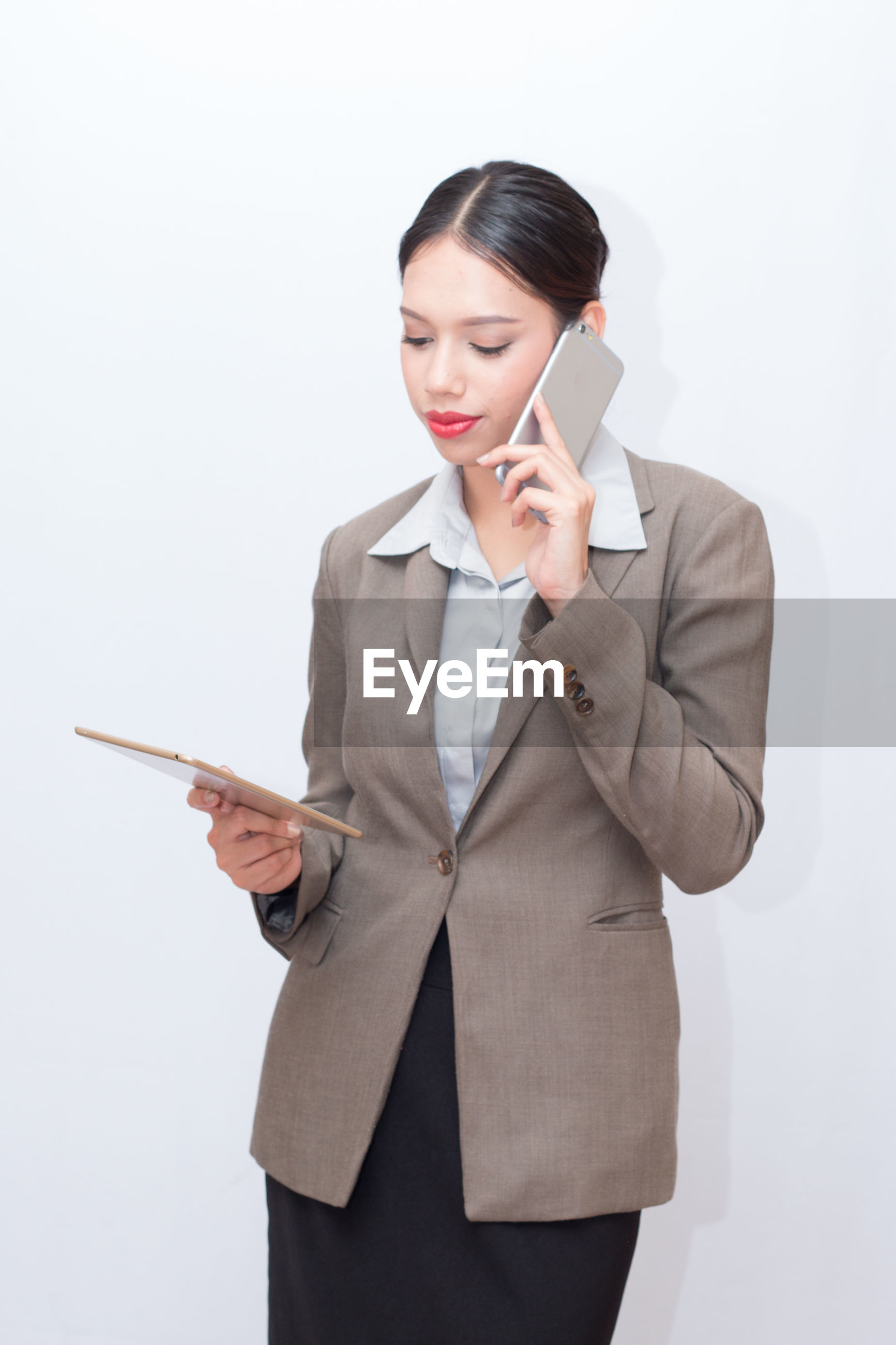 Businesswoman using digital tablet and mobile phone against white background