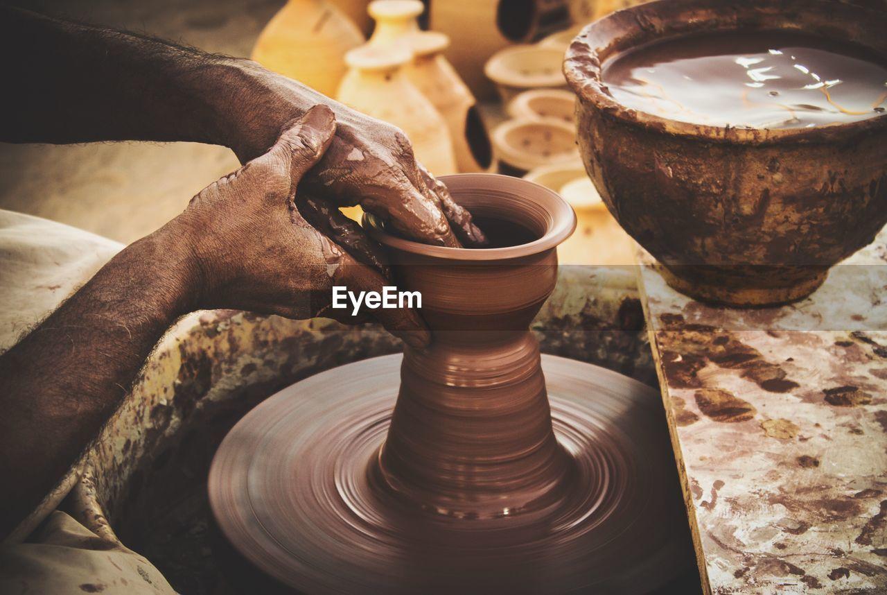 Cropped image of hands making earthen pots on wheel at workshop