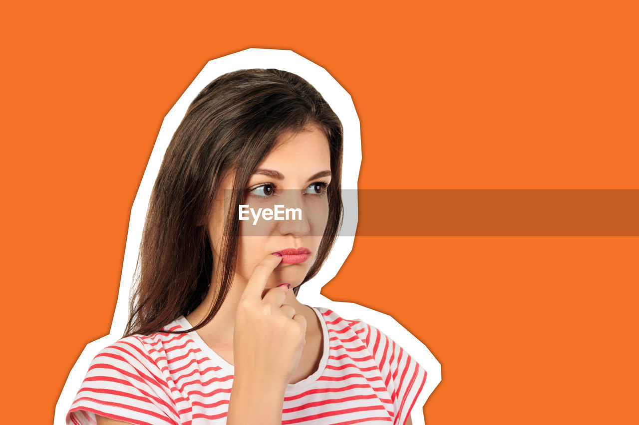 Sad young woman looking away against orange background