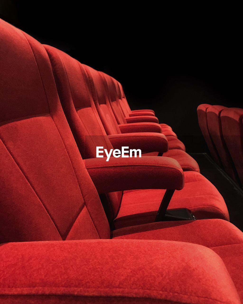 red, seat, in a row, chair, movie theater, empty, arts culture and entertainment, absence, indoors, no people, film industry, auditorium, relaxation, repetition, comfortable, order, theater, dark, black background, stage theater, stage