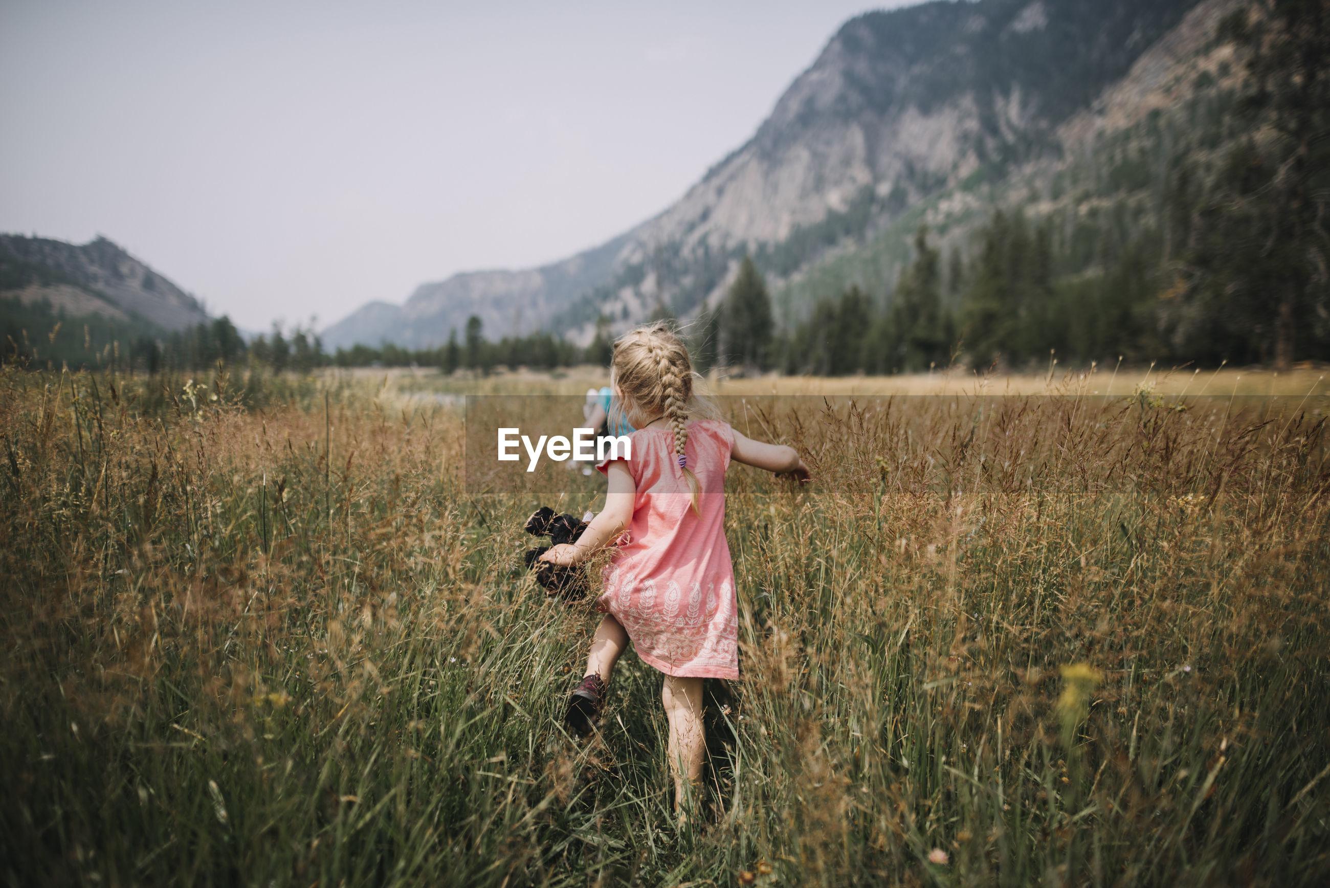 REAR VIEW OF WOMAN ON FIELD