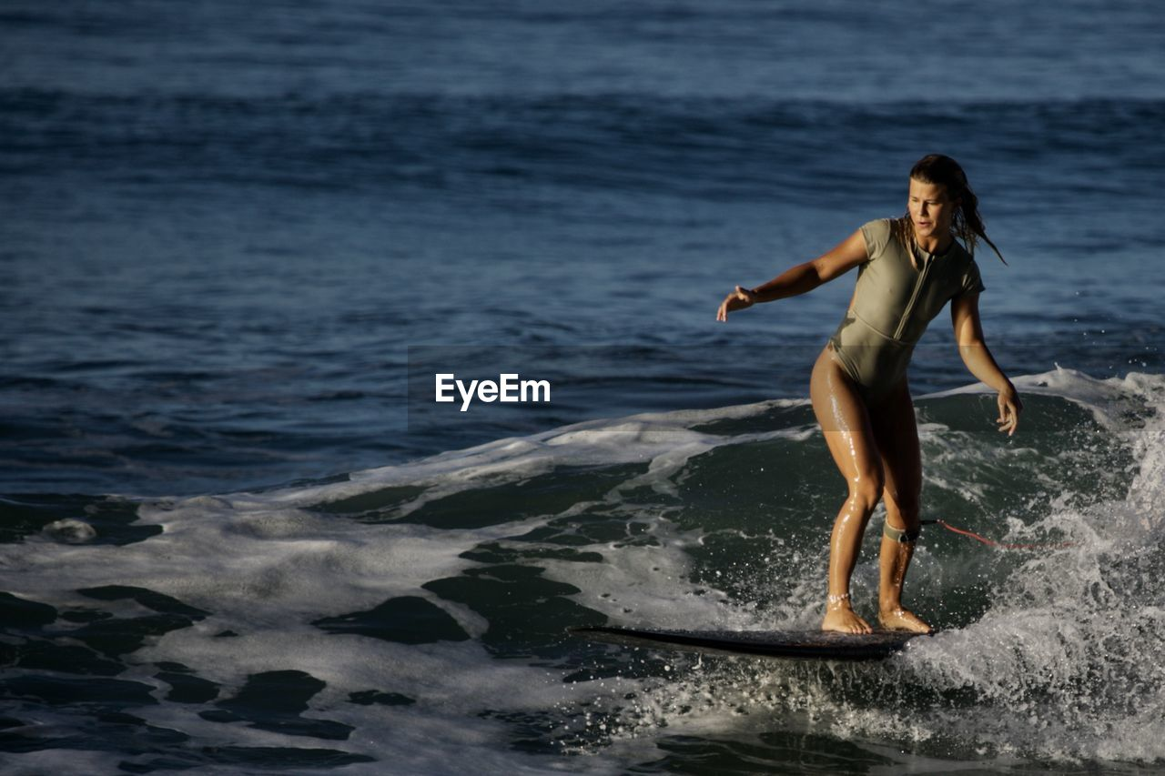 sea, water, full length, motion, one person, beach, lifestyles, young adult, leisure activity, land, wave, sport, women, young women, nature, real people, beauty in nature, standing