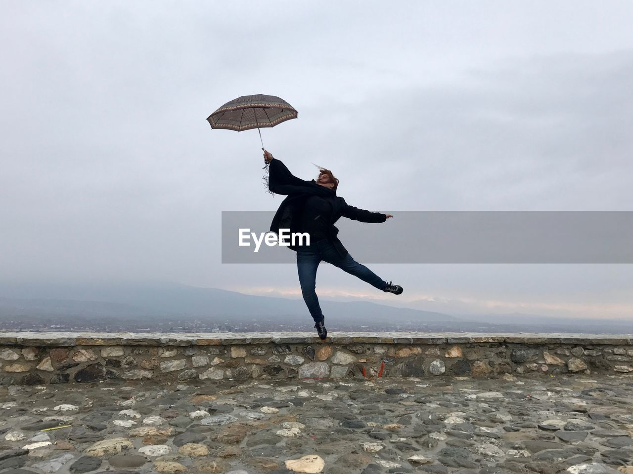 Full Length Of Young Woman Jumping With Umbrella On Retaining Wall Against Sky