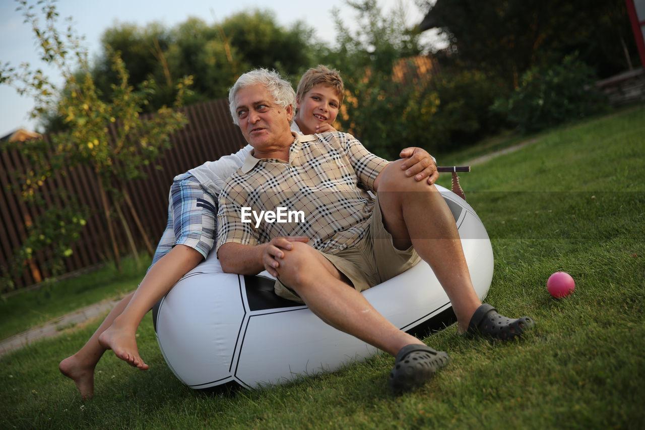 Tilt Shot Of Grandfather And Grandson On Bean Bag At Back Yard
