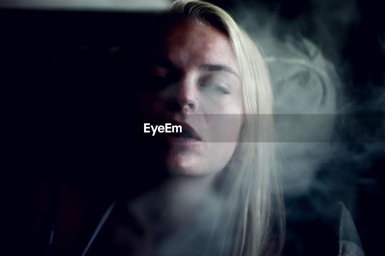 Young woman exhaling smoke