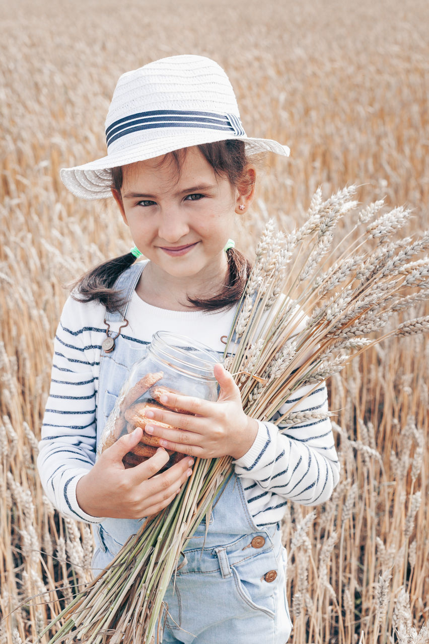 field, plant, agriculture, holding, one person, land, rural scene, front view, standing, farm, nature, crop, looking at camera, child, hat, smiling, lifestyles, casual clothing, leisure activity, real people, outdoors, teenager