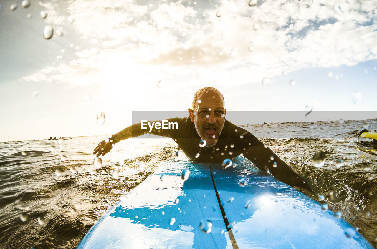 Mature Man Surfing In Sea Against Sky